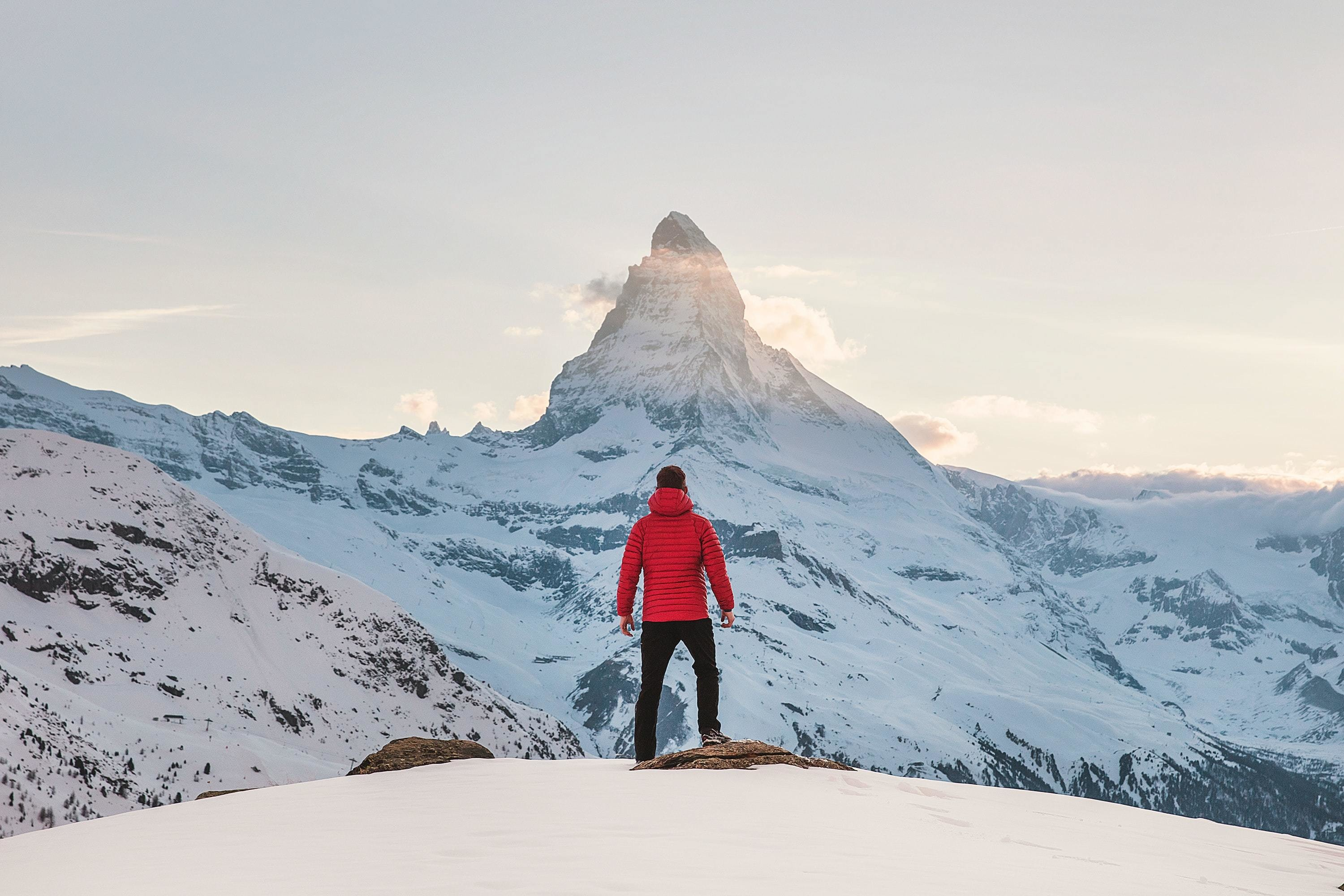 Man standing in red coat looking at the Matterhorn.