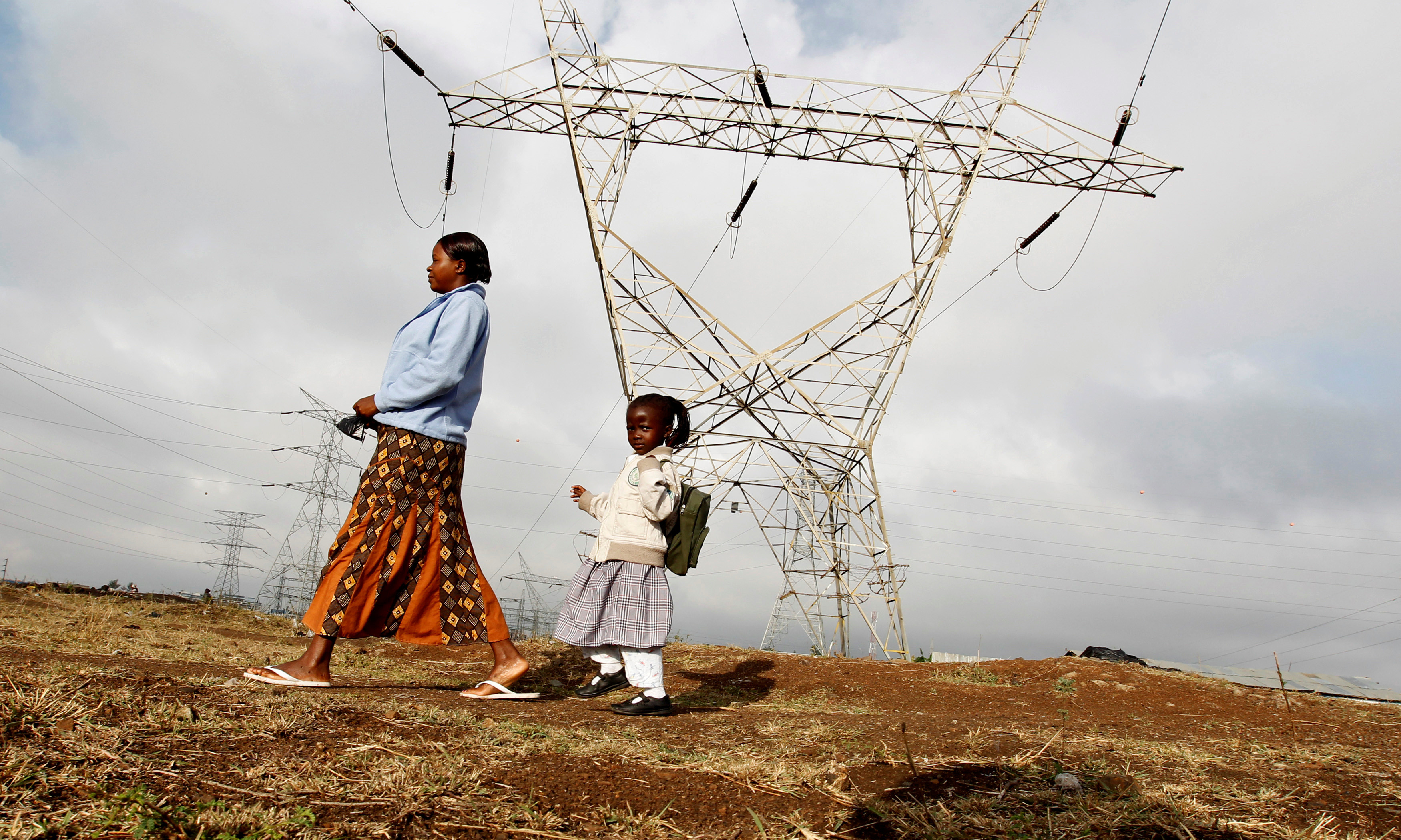 A woman walks her child to school past high voltage electrical pylons on the outskirts of Kenya's capital Nairobi, March 14, 2011
