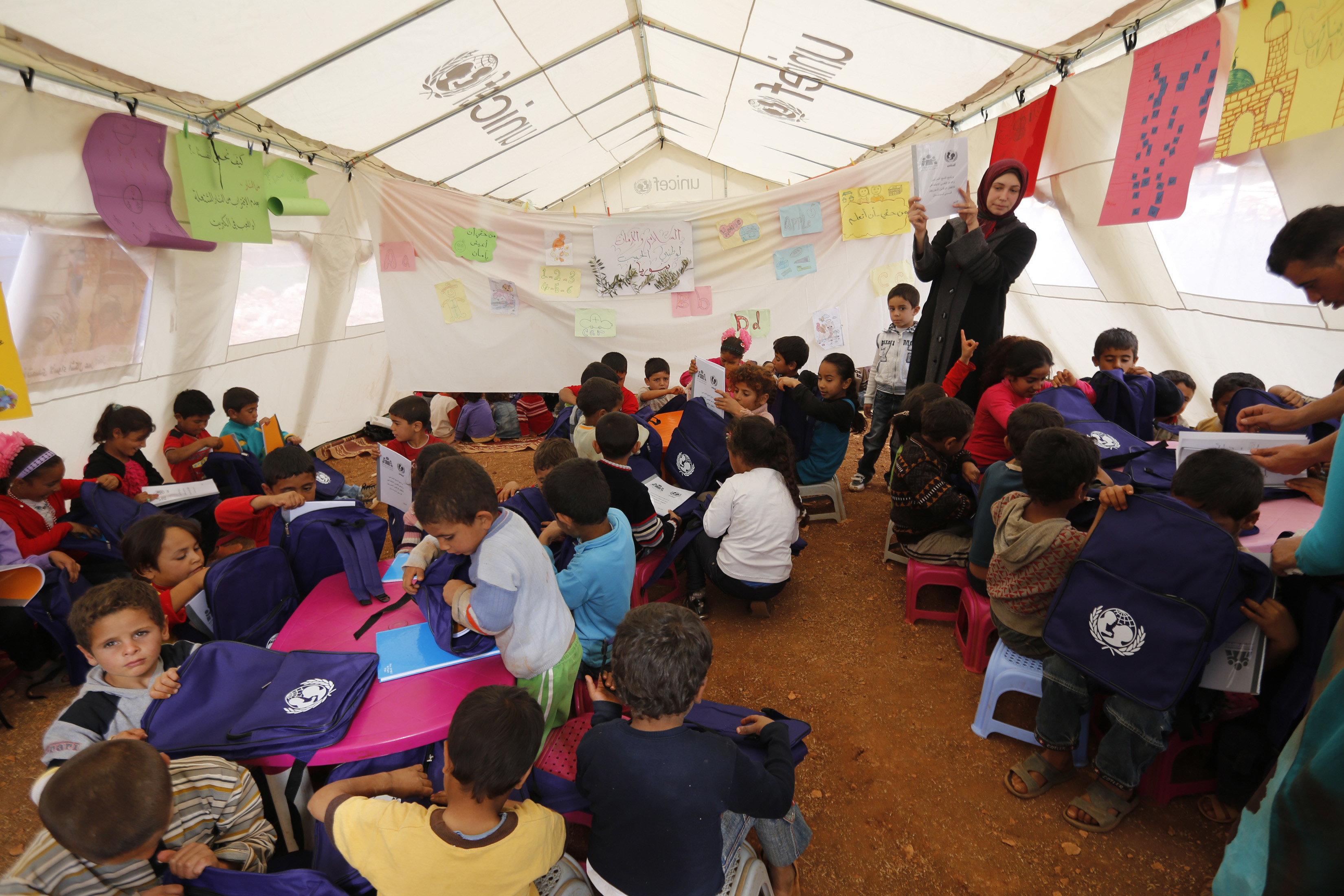 Syrian refugee children sit inside a makeshift school tent as a teacher conducts English lessons during a visit by UNICEF Executive Director Anthony Lake to the Syrian refugees camp in Kfar Zabad village at Bekaa valley, eastern Lebanon, November 1, 2013. International donors must do more to help Lebanon absorb a flood of refugees straining its schools and public services, the head of the United Nations children's fund UNICEF said. Picture taken November 1, 2013. REUTERS/Jamal Saidi (LEBANON - Tags: CIVIL UNREST POLITICS SOCIETY EDUCATION) - GM1E9B31M8L01