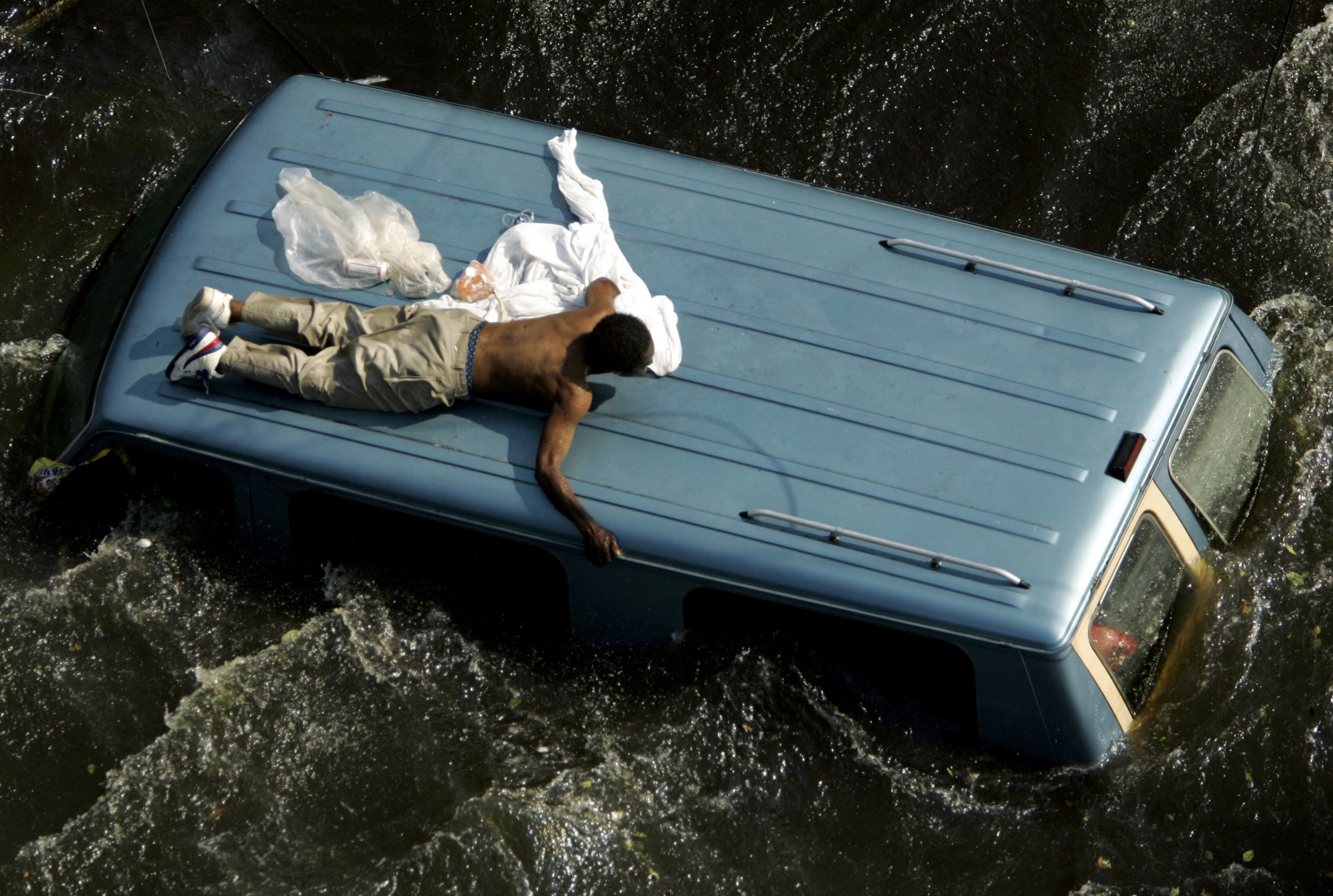 a man clings to the top of a vehicle before being rescued by the U.S. Coast Guard from the flooded streets of New Orleans, in the aftermath of Hurricane Katrina