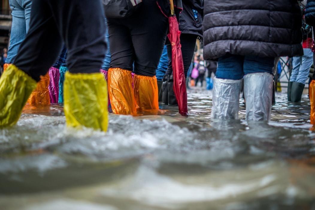 image of people wearing plastic footwear/leg protectors against flooding in Venice, Italy