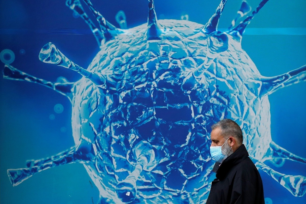 A man wearing a protective face mask walks past an illustration of a virus outside a regional science centre, as the city and surrounding areas face local restrictions in an effort to avoid a local lockdown being forced upon the region, amid the coronavirus disease (COVID-19) outbreak, in Oldham, Britain August 3, 2020. REUTERS/Phil Noble - RC2A6I9OAYDW