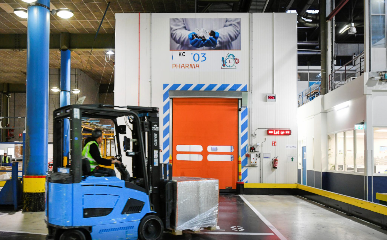 A KLM worker is entering a cold room by forklift in operation for a massive logistical operation carrying vaccines.