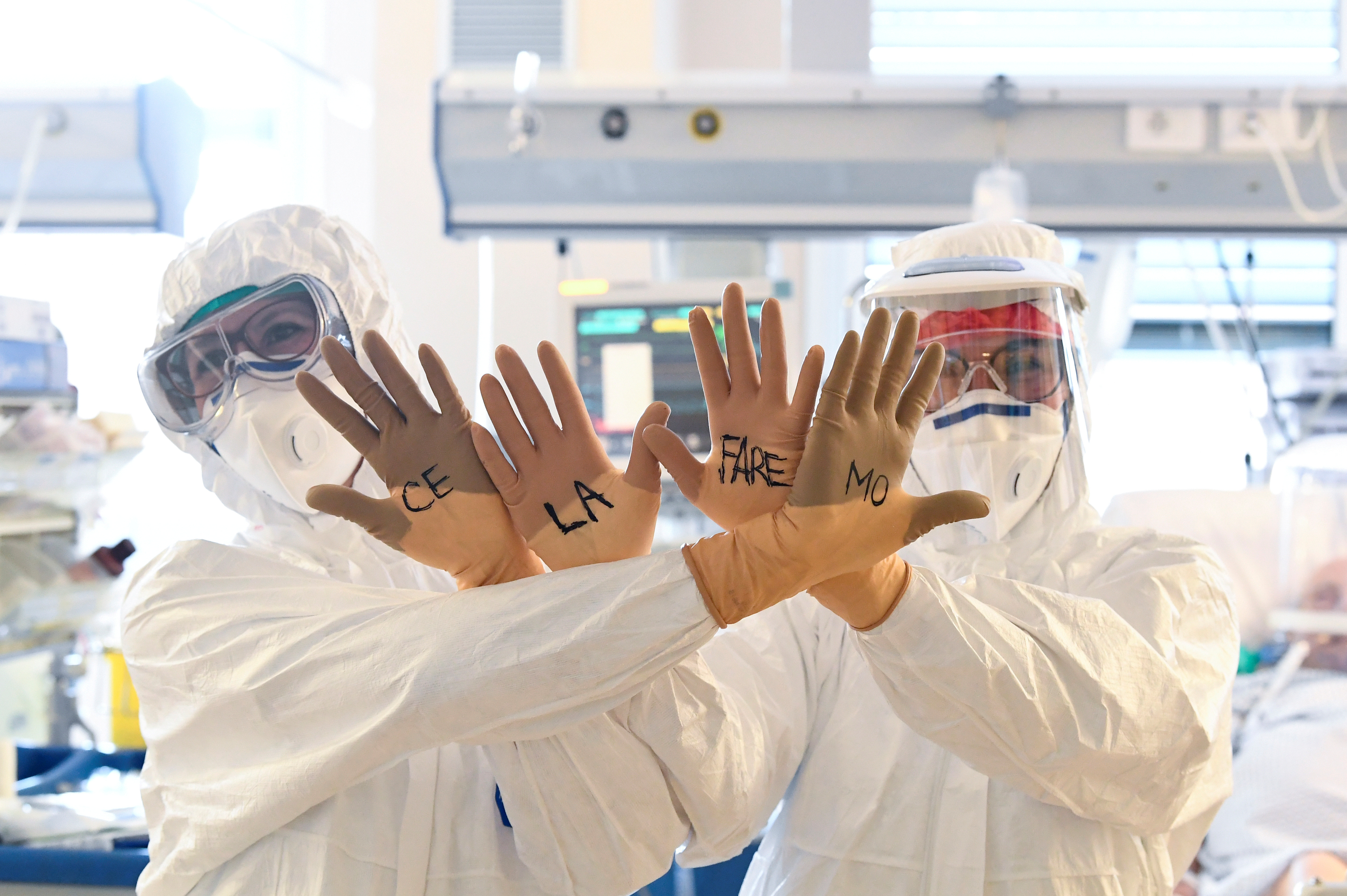 """Medical staff members wearing protective gear show their hands with the words written on gloves """"Ce la faremo"""" (""""We'll make it"""") written on them as they treat patients suffering from the coronavirus disease (COVID-19) in the intensive care unit at the Circolo hospital in Varese, Italy April 9, 2020. REUTERS/Flavio Lo Scalzo"""
