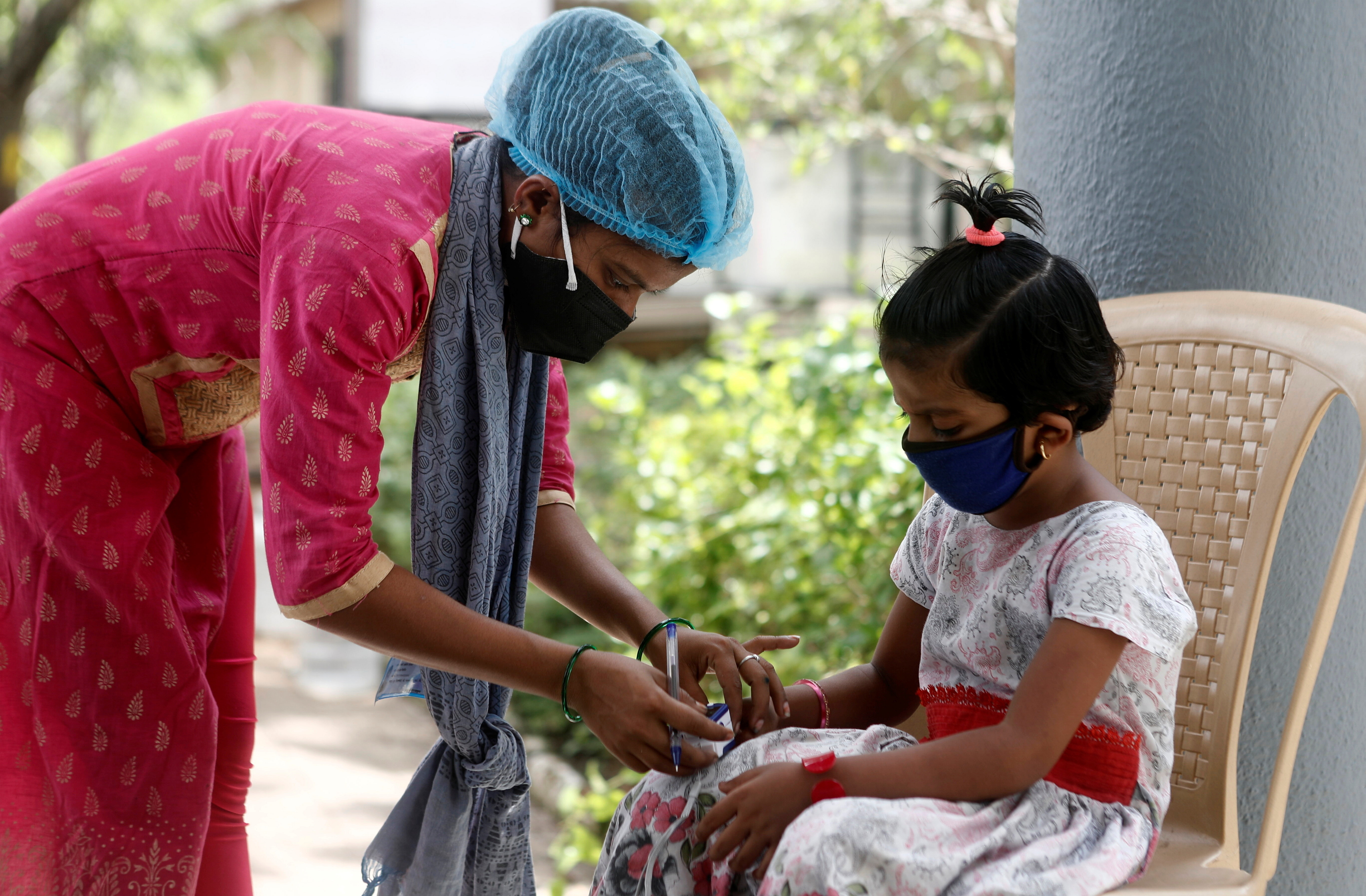 A nurse checks a coronavirus disease patient's pulse before she is admitted into a school turned COVID-19 care facility on the outskirts of Mumbai, India, May 24, 2021. REUTERS/Francis Mascarenhas - RC25MN9WTO0L