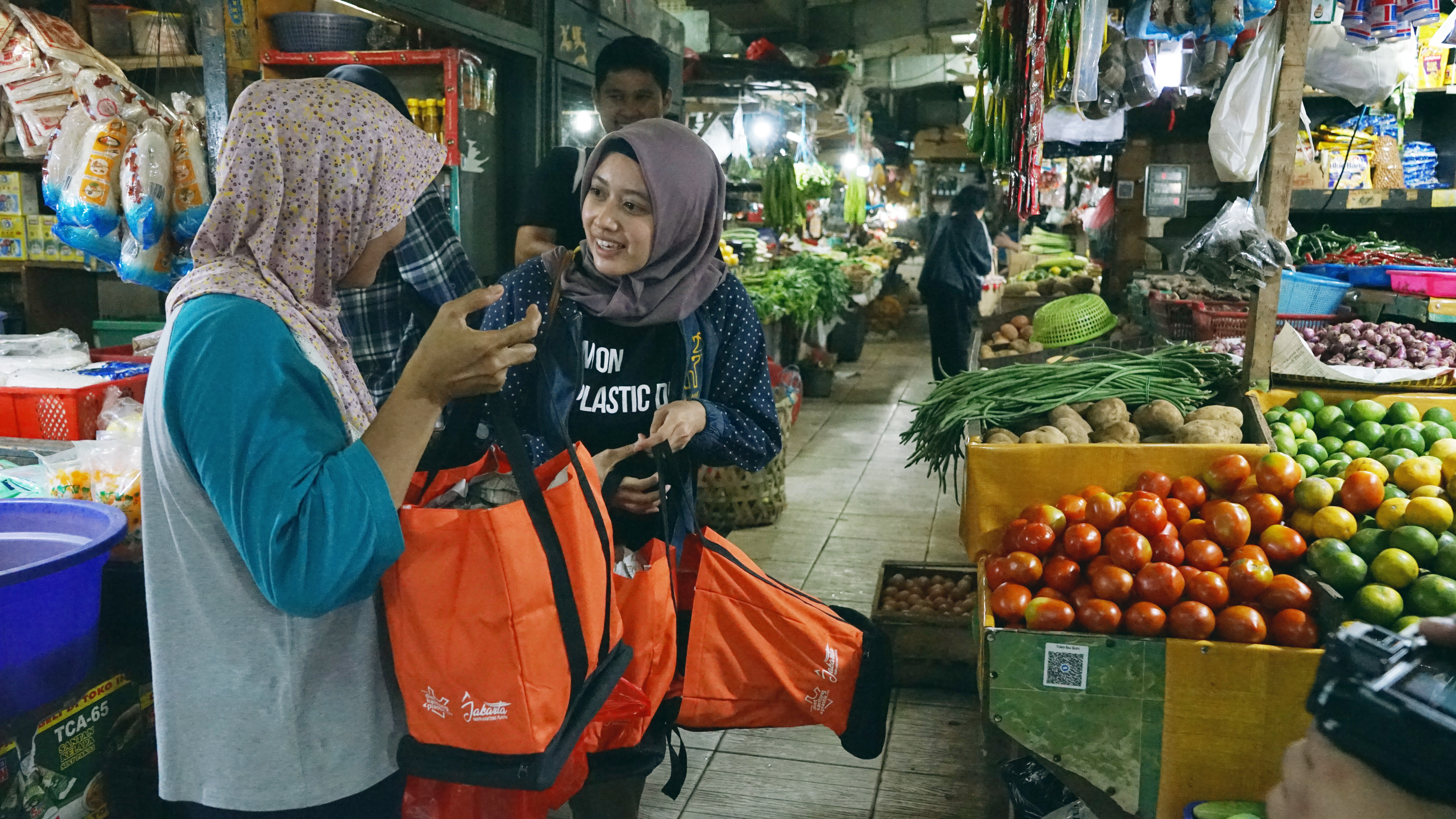 A young campaigner persuades a shopper in Jakarta to swap her plastic shopping bag for a reusable one.