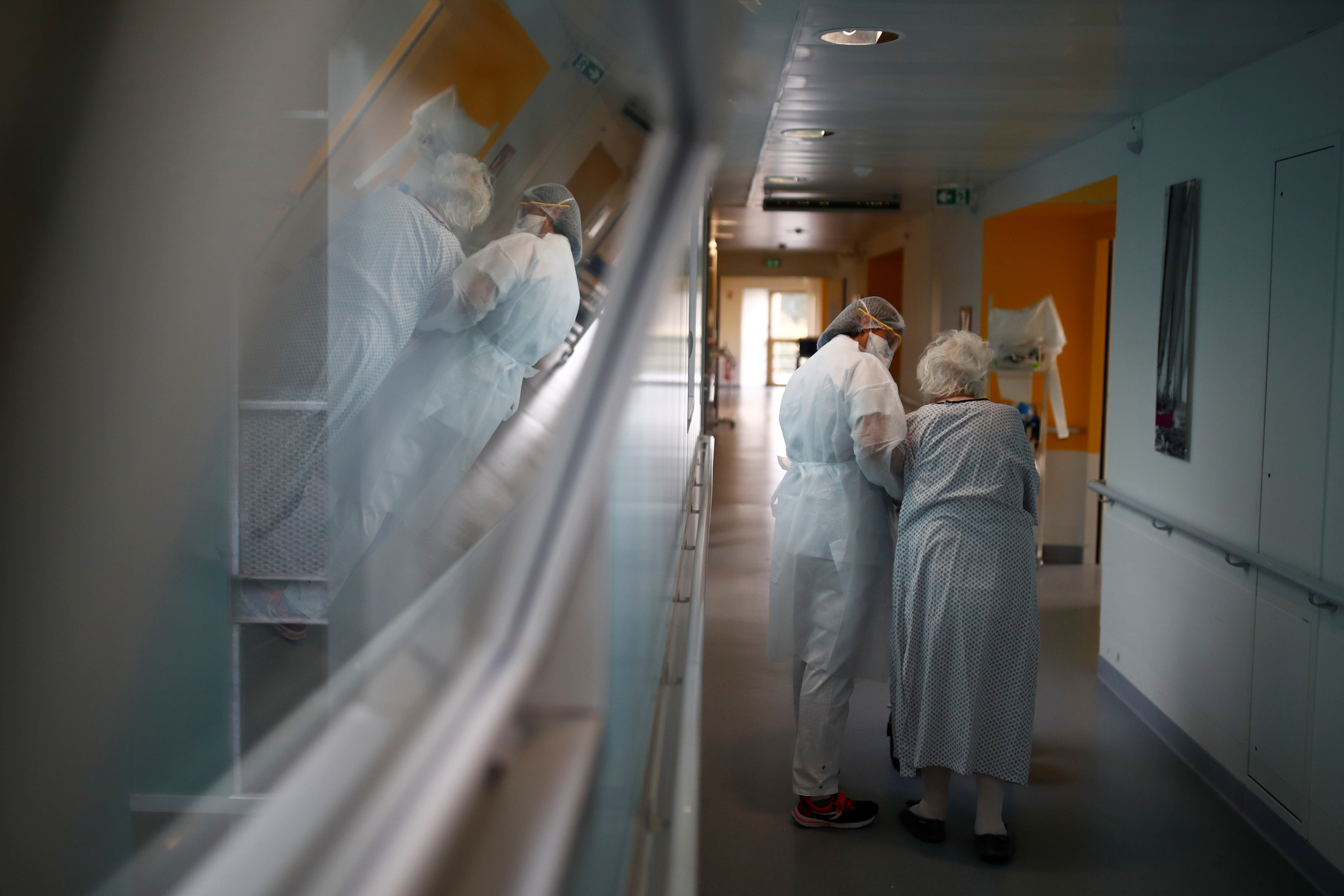 A physiotherapist, wearing a protective mask and a protective suit, works in a pulmonology unit at the hospital in Vannes where patients suffering from the coronavirus disease (COVID-19) are treated, France, October 12, 2020. REUTERS/Stephane Mahe