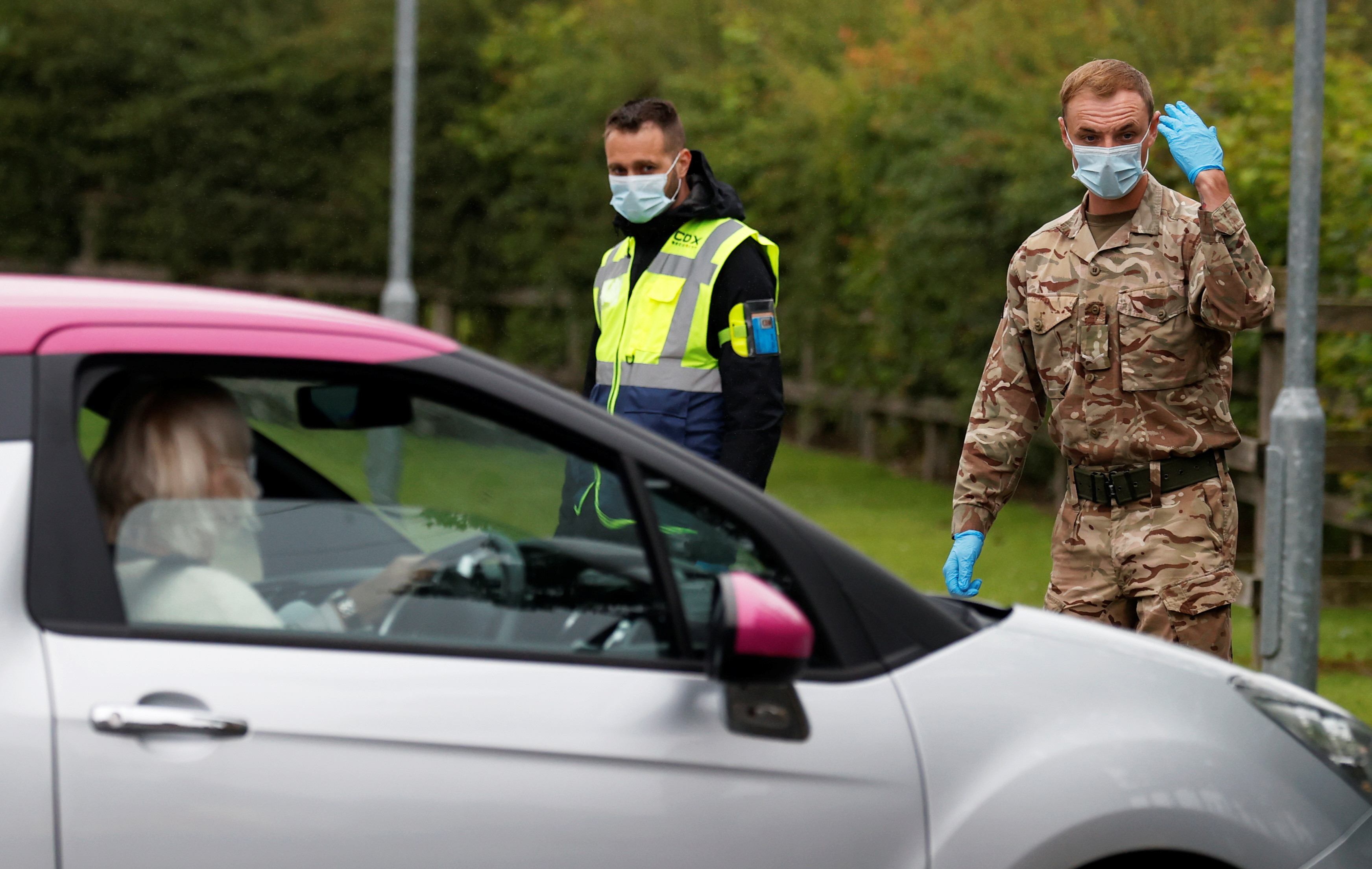 A soldier wearing a protective mask gestures as he directs cars into a coronavirus disease (COVID-19) testing center, as Blackburn with Darwen Council imposes local restrictions in an effort to avoid a local lockdown being forced upon the area, amid the coronavirus disease (COVID-19) outbreak, in Blackburn, Britain July 16, 2020. REUTERS/Phil Noble - RC2AUH9DL0IJ