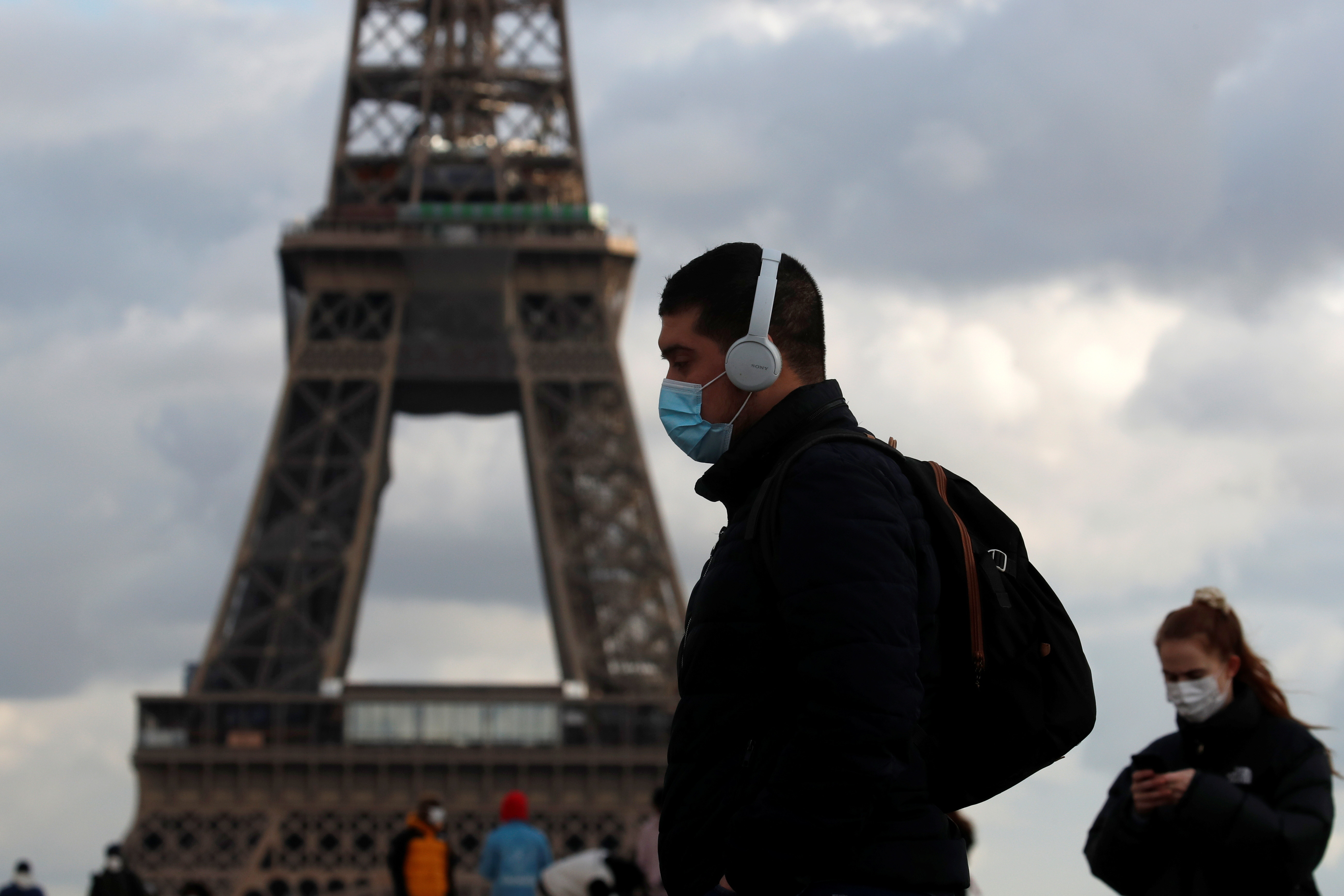People, wearing protective face masks, walk at Trocadero square near the Eiffel Tower in Paris amid the coronavirus disease (COVID-19) outbreak in France, January 22, 2021. REUTERS/Gonzalo Fuentes - RC24DL9LV1PU