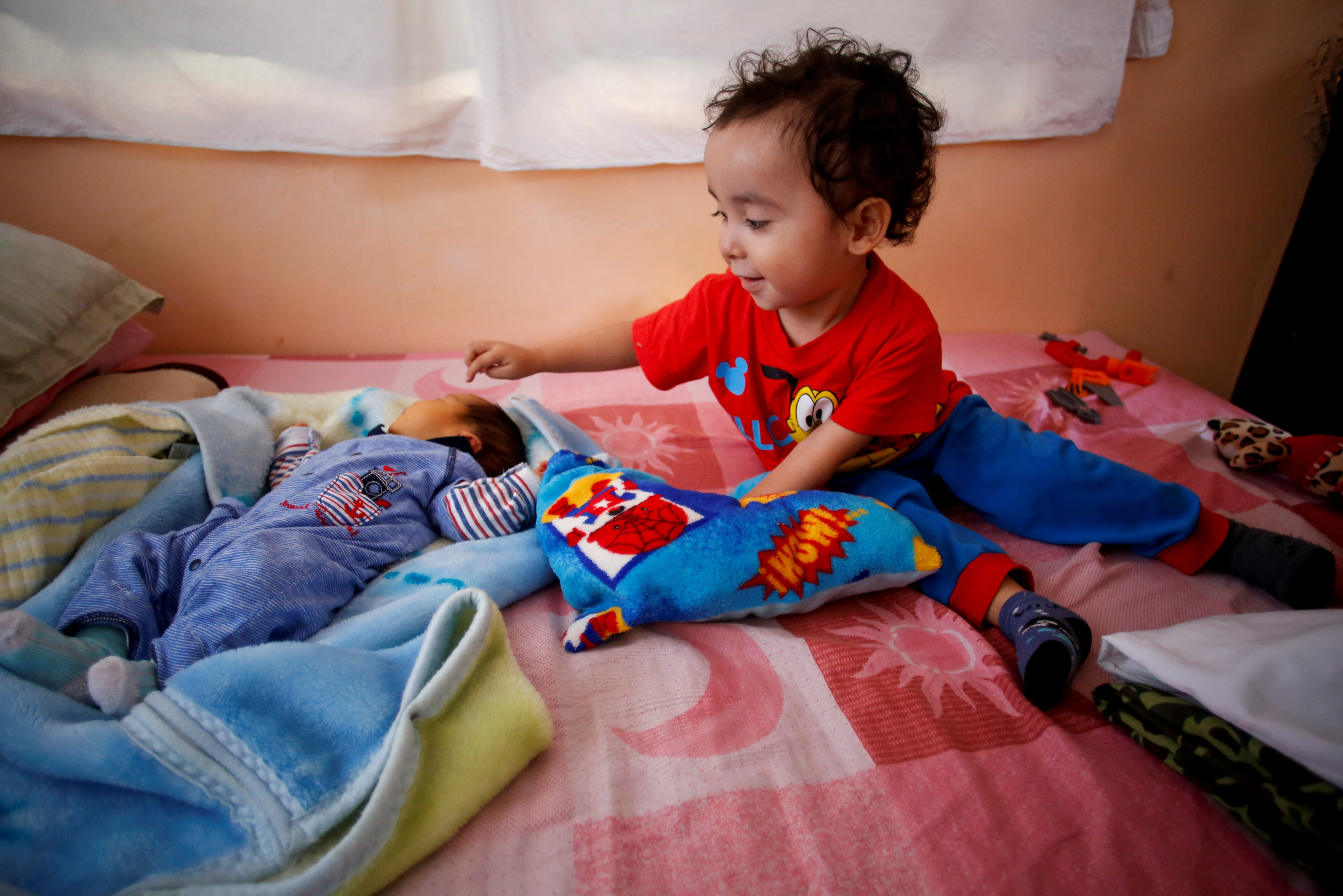 """Angel Flores Lopez, 3, points to his newborn baby brother Sabino Yoehi Flores Lopez as they sit on a bed at their grandparent's apartment, where they are staying with their parents after their mother Karla Lopez Rangel gave birth to Sabino at home during the coronavirus disease (COVID-19) outbreak, in Iztapalapa, Mexico City, Mexico, June 4, 2020. REUTERS/Gustavo Graf     SEARCH """"COVID-19 MEXICO BIRTH"""" FOR THIS STORY. SEARCH """"WIDER IMAGE"""" FOR ALL STORIES. - RC2ACH9NFQHS"""
