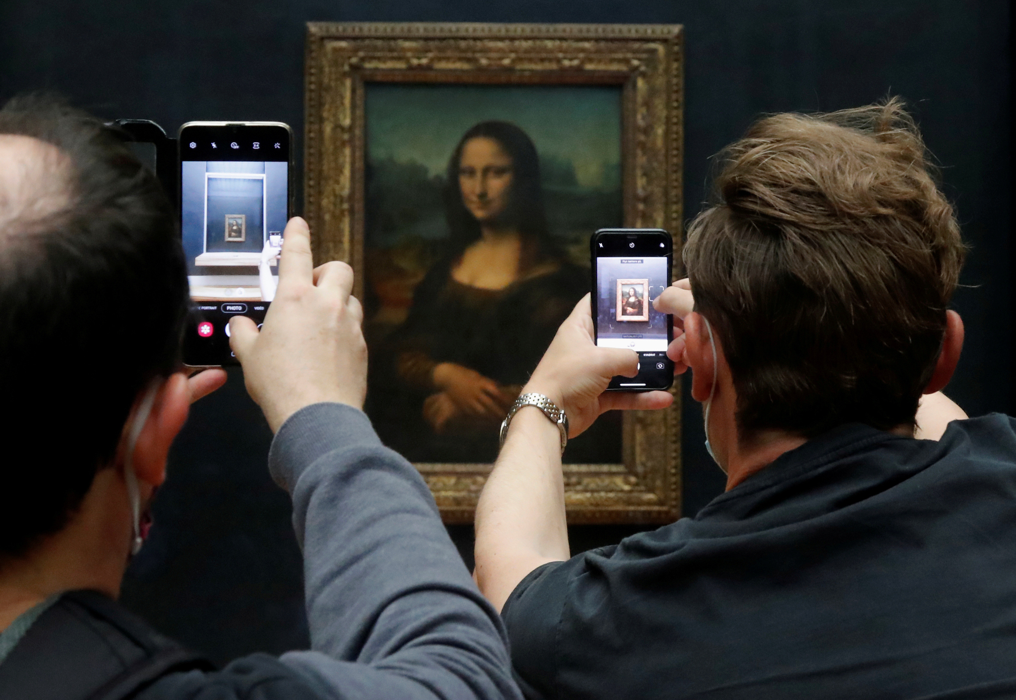 """Visitors take pictures of the painting """"Mona Lisa"""" (La Joconde) by Leonardo da Vinci at the Louvre museum in Paris as the museum reopens its doors to the public after an almost four-month closure due to the coronavirus disease (COVID-19) outbreak in France, July 6, 2020. REUTERS/Charles Platiau     TPX IMAGES OF THE DAY - RC2MNH9MZ98D"""