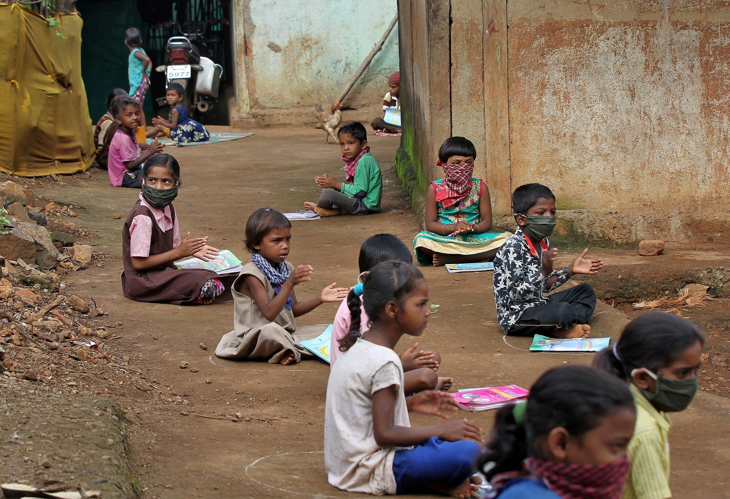 Children, who have missed their online classes due to a lack of internet facilities, sit on the ground in circles drawn with chalk to maintain a safe distance, as they listen to pre-recorded lessons over loudspeakers, after schools were closed following the coronavirus disease (COVID-19) outbreak, in Dandwal village in the western state of Maharashtra, India, July 23, 2020. Picture taken July 23, 2020. REUTERS/Prashant Waydande - RC2P6I92PEZD