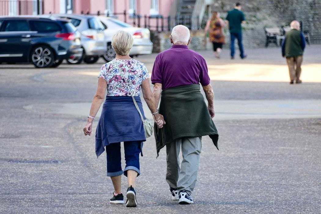 image of two elderly people working together