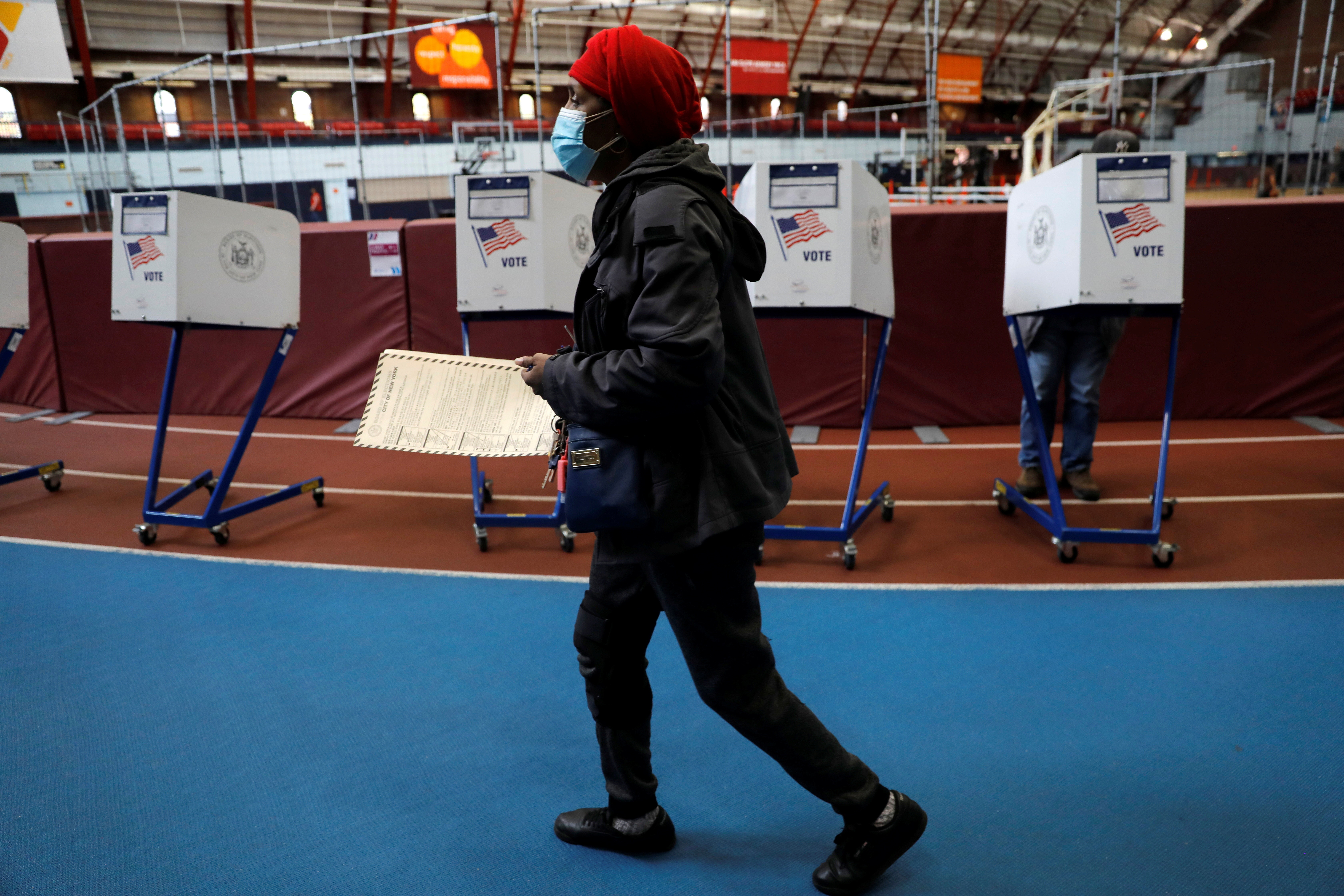 A woman carries her ballot to fill it out in a voting booth at the Brooklyn Armory after waiting several hours in line with hundreds of other voters during early voting in the Brooklyn borough of New York City, New York, U.S., October 27, 2020. REUTERS/Mike Segar - RC2ARJ9CB9OF