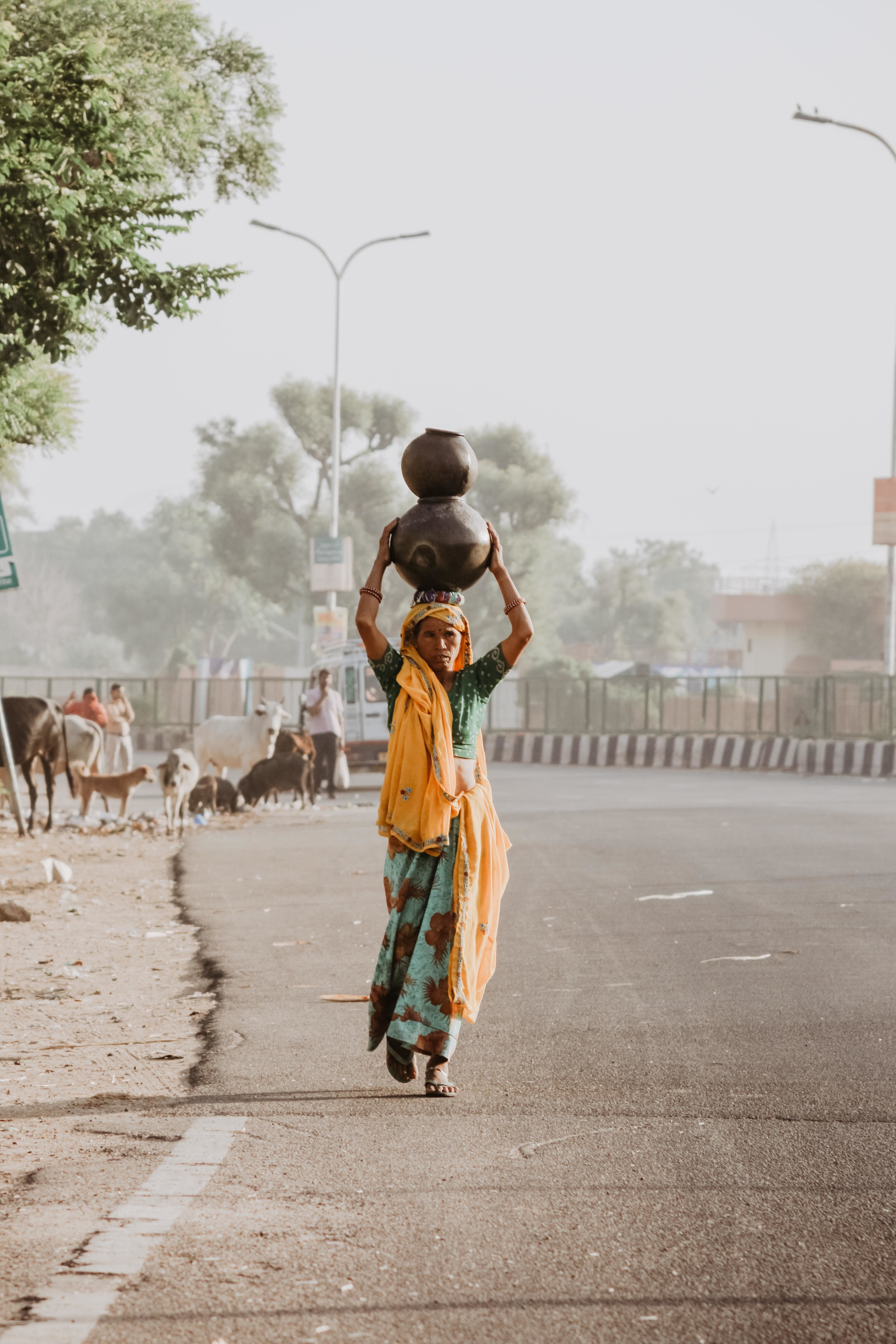 An Indian woman carries a jar of water on her head