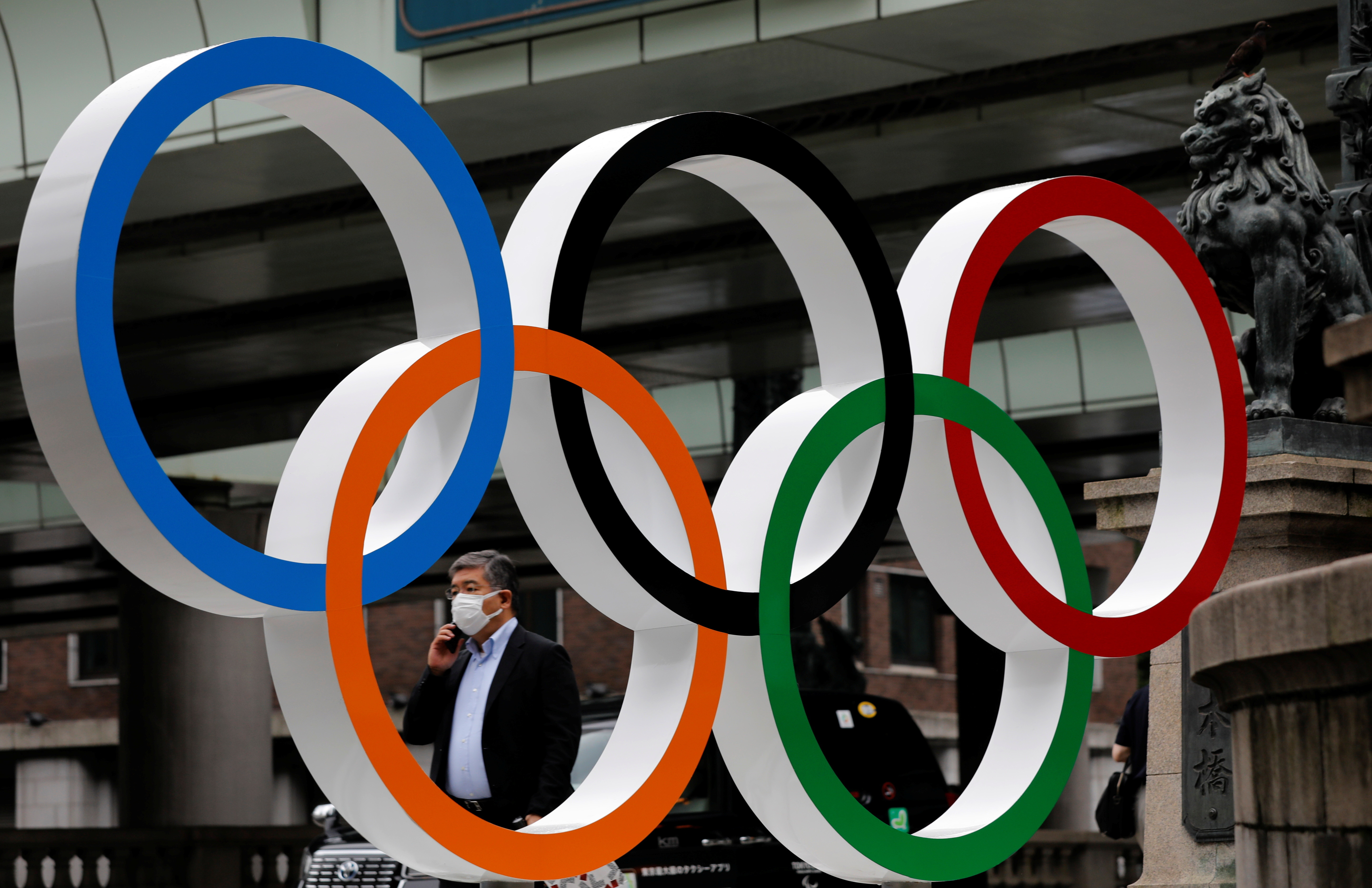 A man wearing a protective mask, following the COVID-19 outbreak, walks past Olympic Ring promoting Tokyo 2020 Olympic Games in Tokyo, Japan