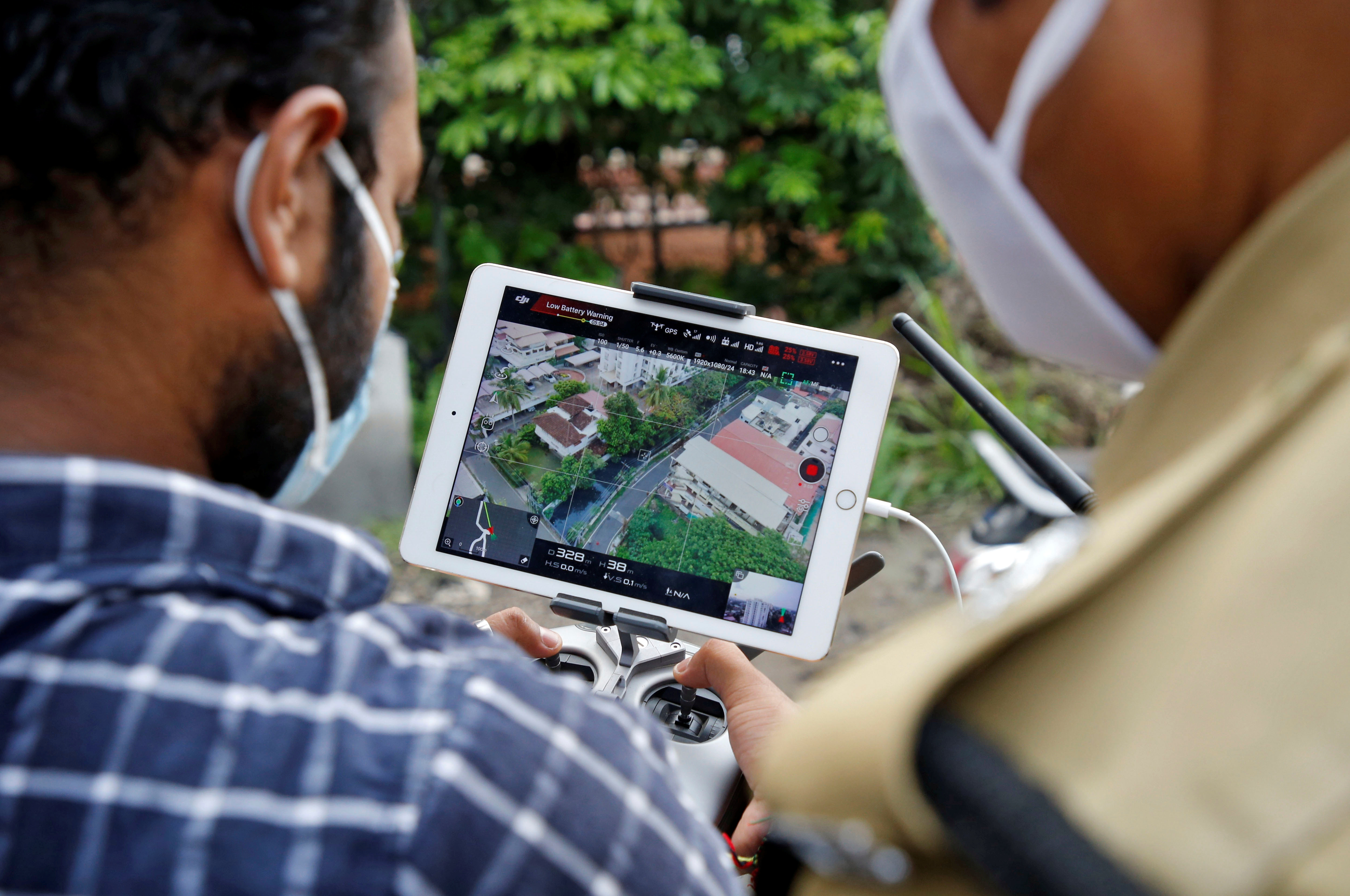 Police officers use a drone to monitor the movement of people in a residential area after the area was declared a hot spot by government officials during a nationwide lockdown to slow the spreading of the coronavirus disease (COVID-19) in Kochi, India, April 24, 2020. REUTERS/Sivaram V - RC2VAG90QXTN