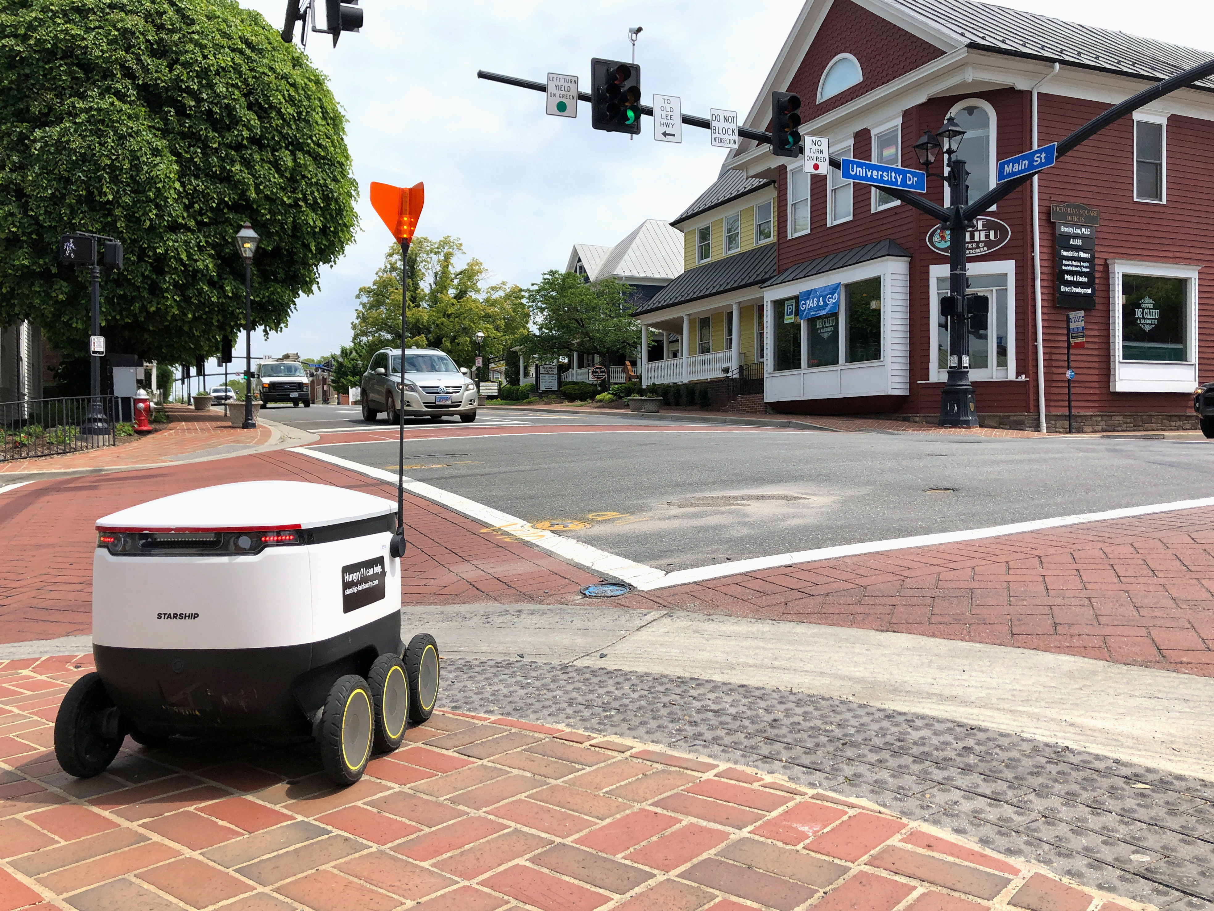 A Starship delivery robot waits to cross an intersection as it drives itself to deliver food amid the coronavirus disease (COVID-19) outbreak in Fairfax, Virginia, U.S., May 15, 2020.   REUTERS/Julio-Cesar Chavez - RC27RG902W0P
