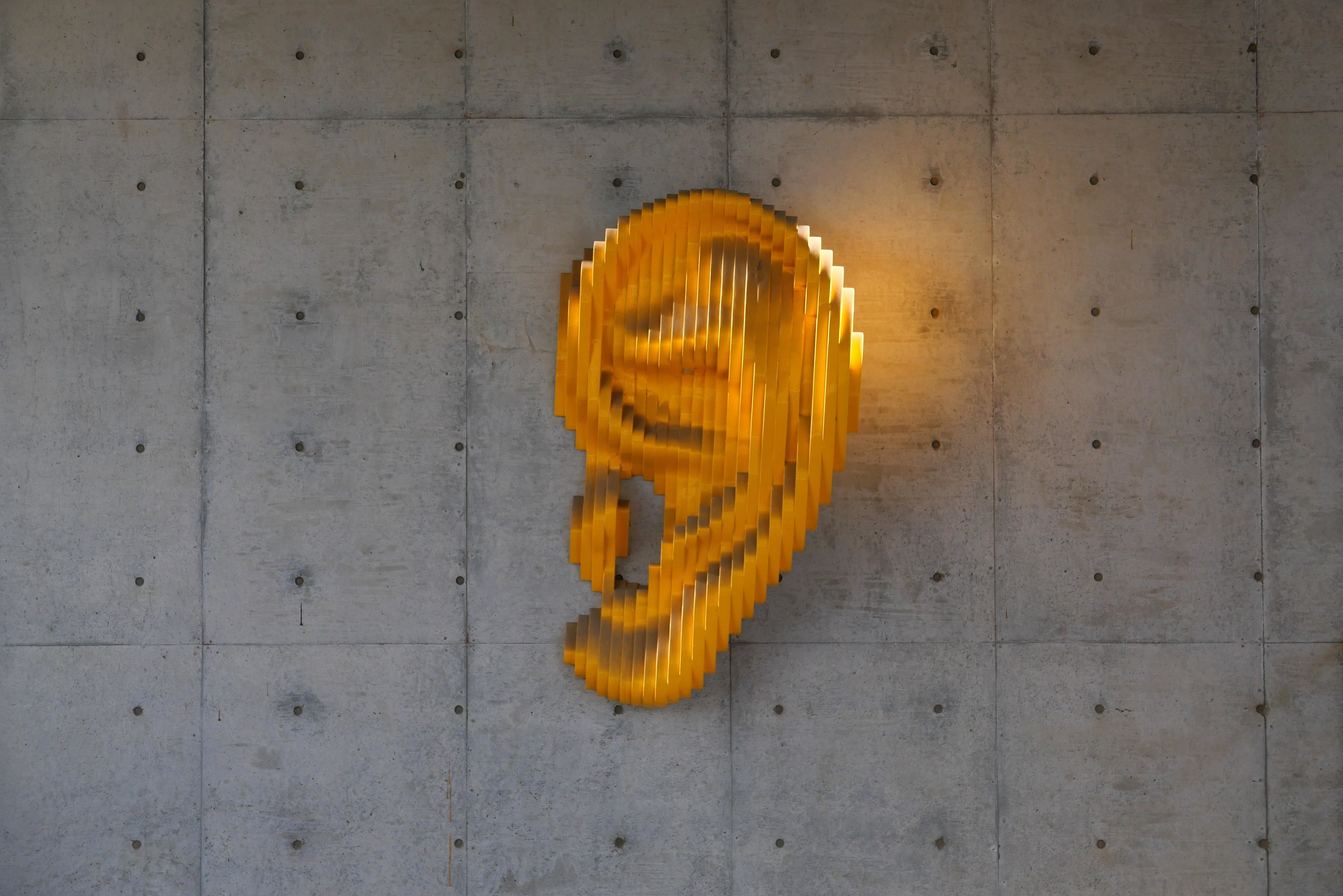 A sculpture of a golden ear, listening to a podcast, perhaps?