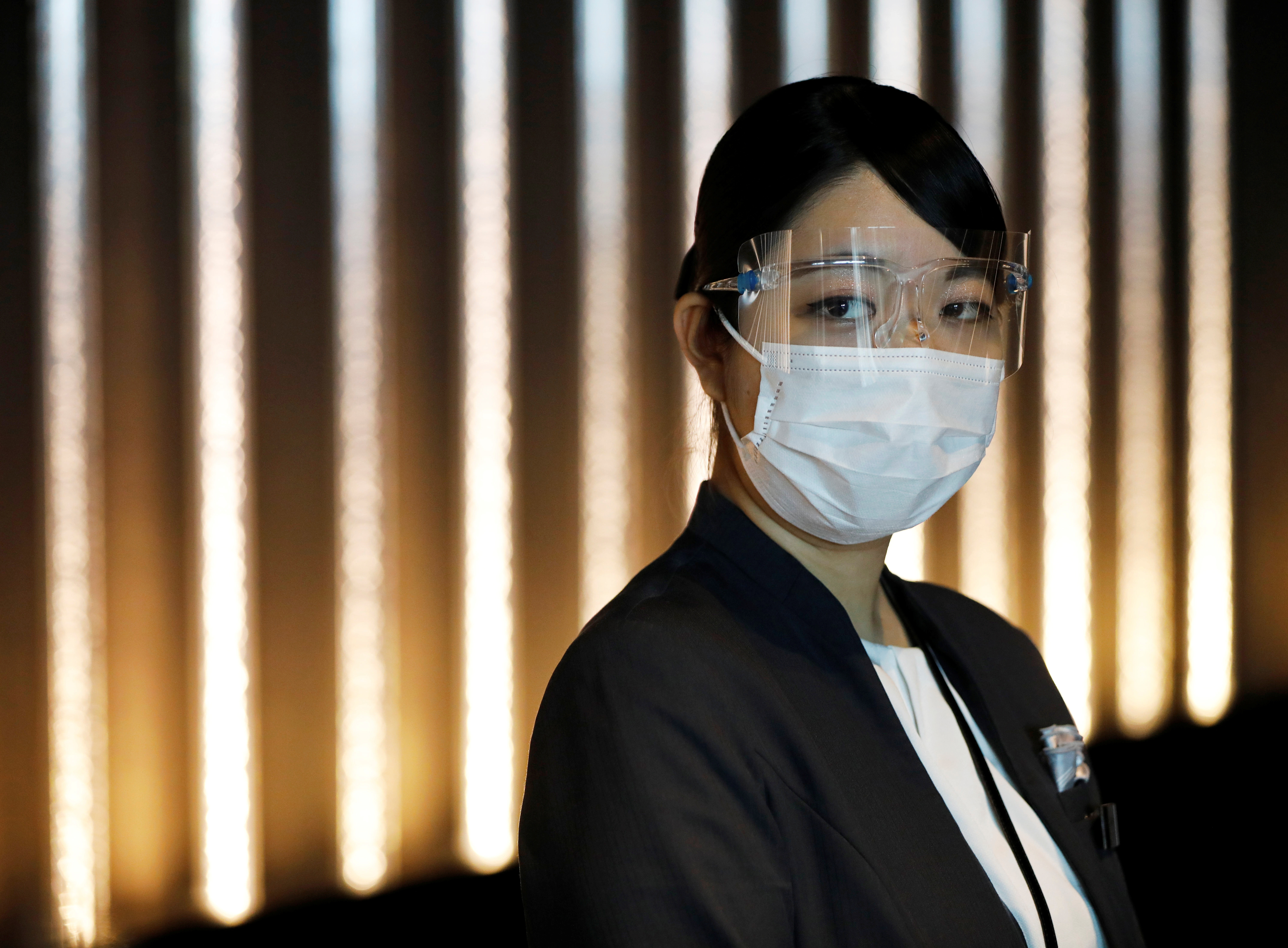 A hotel worker wears a protective mask and goggles at the reception desk of Mitsui Garden Hotel Nihonbashi Premier during the spread of the coronavirus disease (COVID-19) in Tokyo, Japan June 26, 2020.