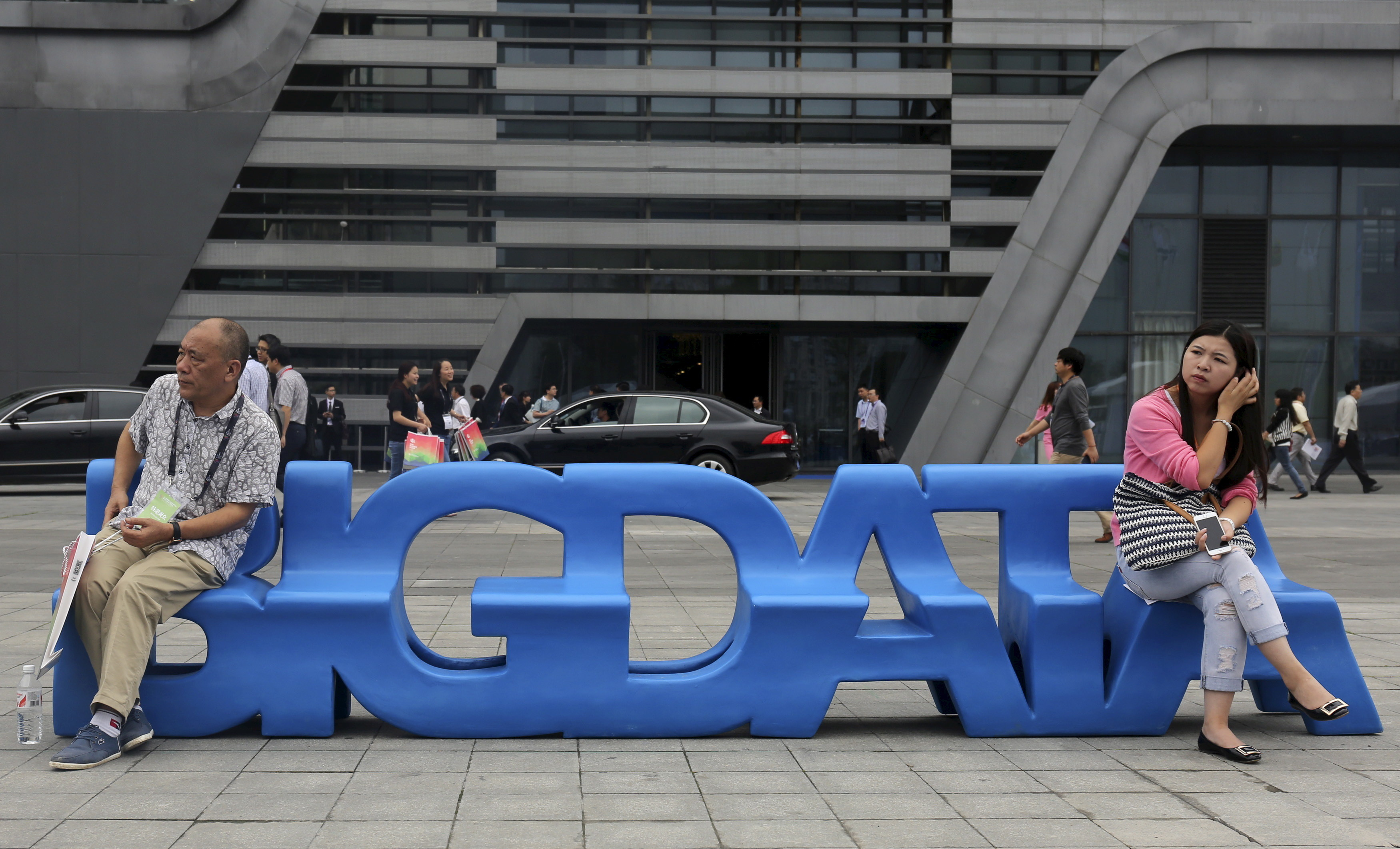 "Visitors sit on a bench made in the shape of ""Big Data"" outside the venue of the 2015 Big Data Expo in Guiyang, Guizhou province, China, May 26, 2015. Picture taken May 26, 2015. REUTERS/Paul Carsten - GF10000108097"