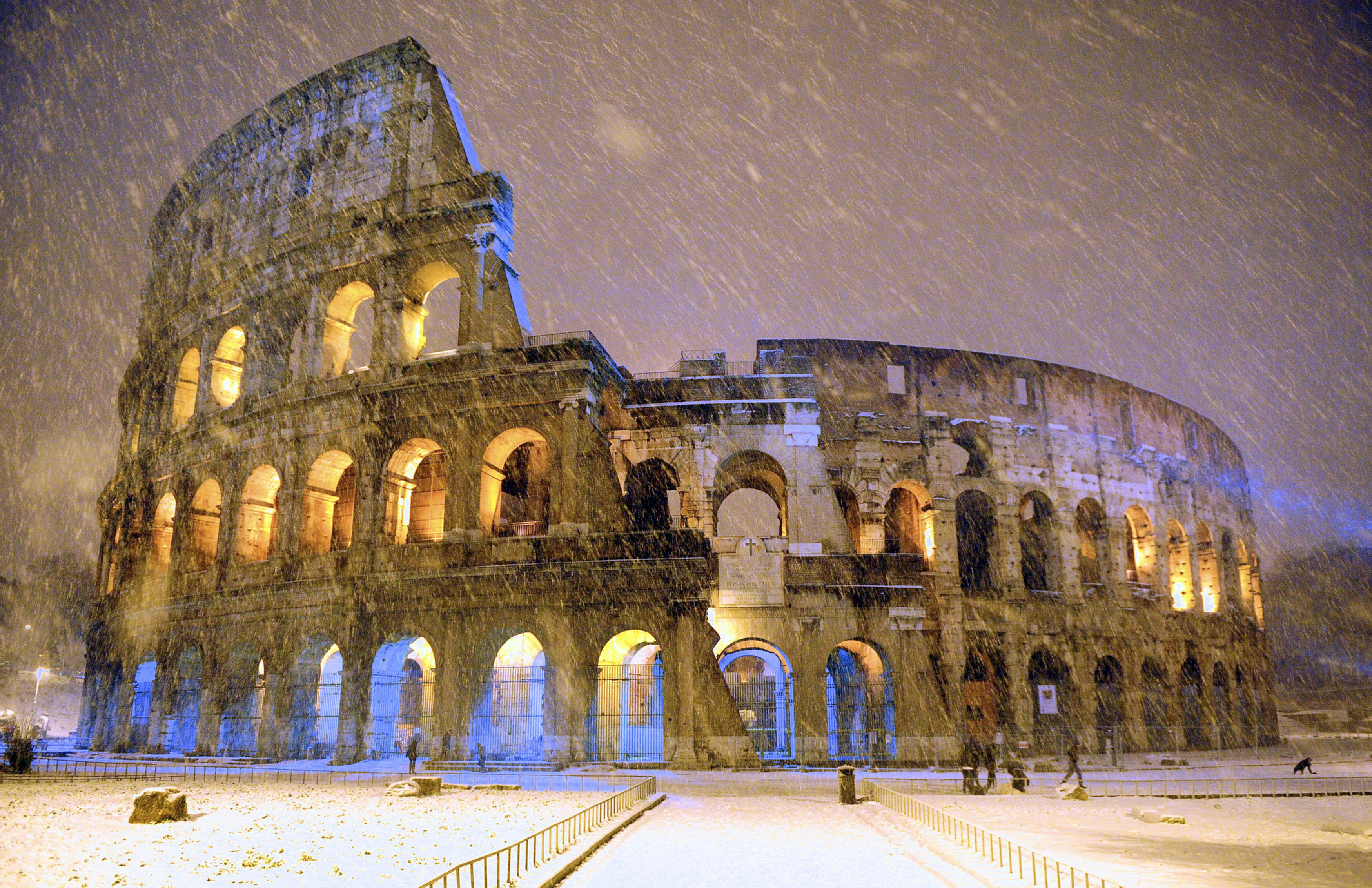 The ancient Colosseum is seen during an heavy snowfalls late in the night  in Rome
