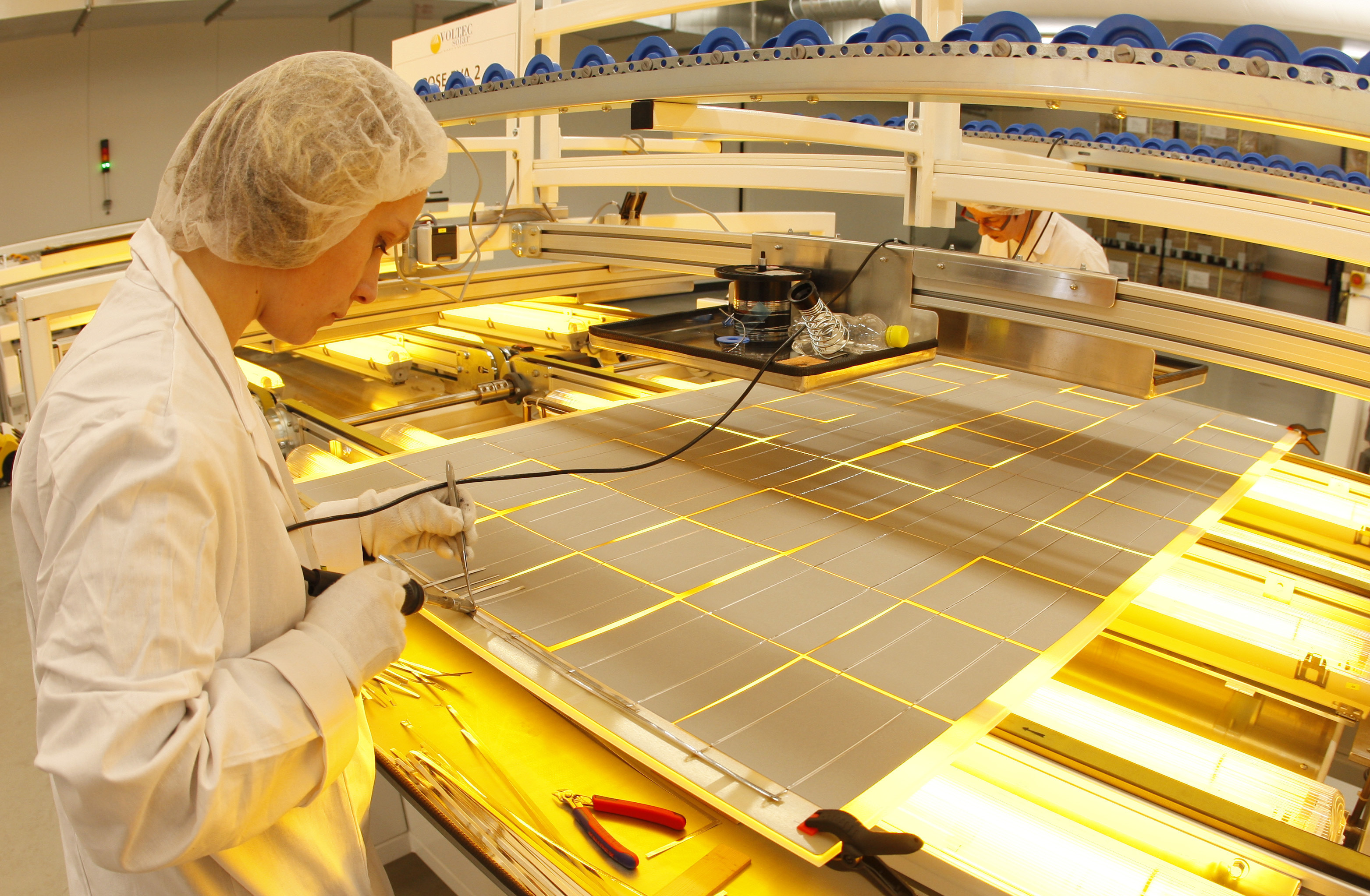 Employees work at the assembly line of photovoltaic panels at the Voltec Solar factory in Dinsheim sur Bruche near Strasbourg, March 11, 2010.  REUTERS/Vincent Kessler   (FRANCE - Tags: BUSINESS ENERGY ENVIRONMENT) - PM1E63B15AI01