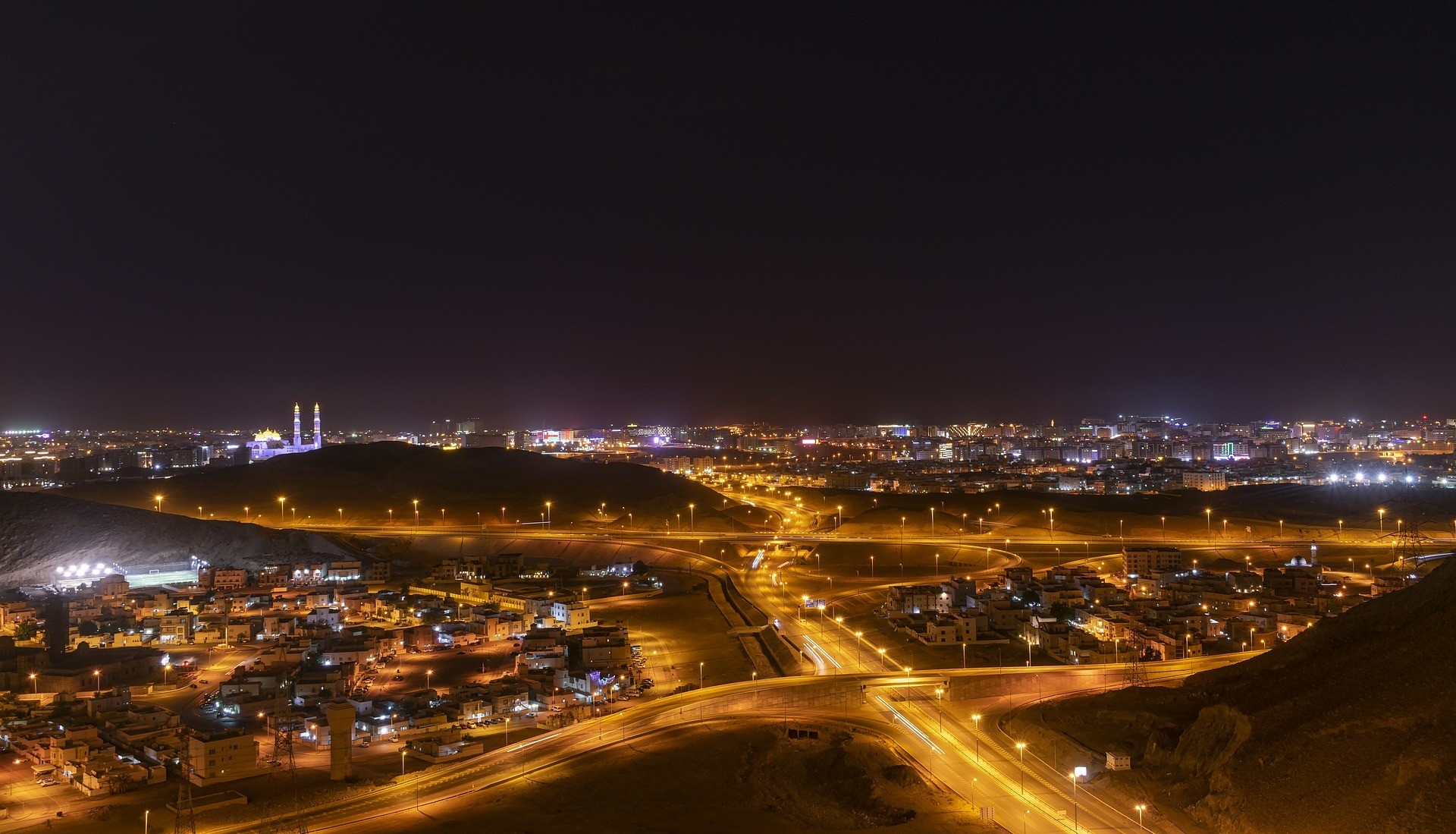 A landscape shot of roads outside a city in Oman at night