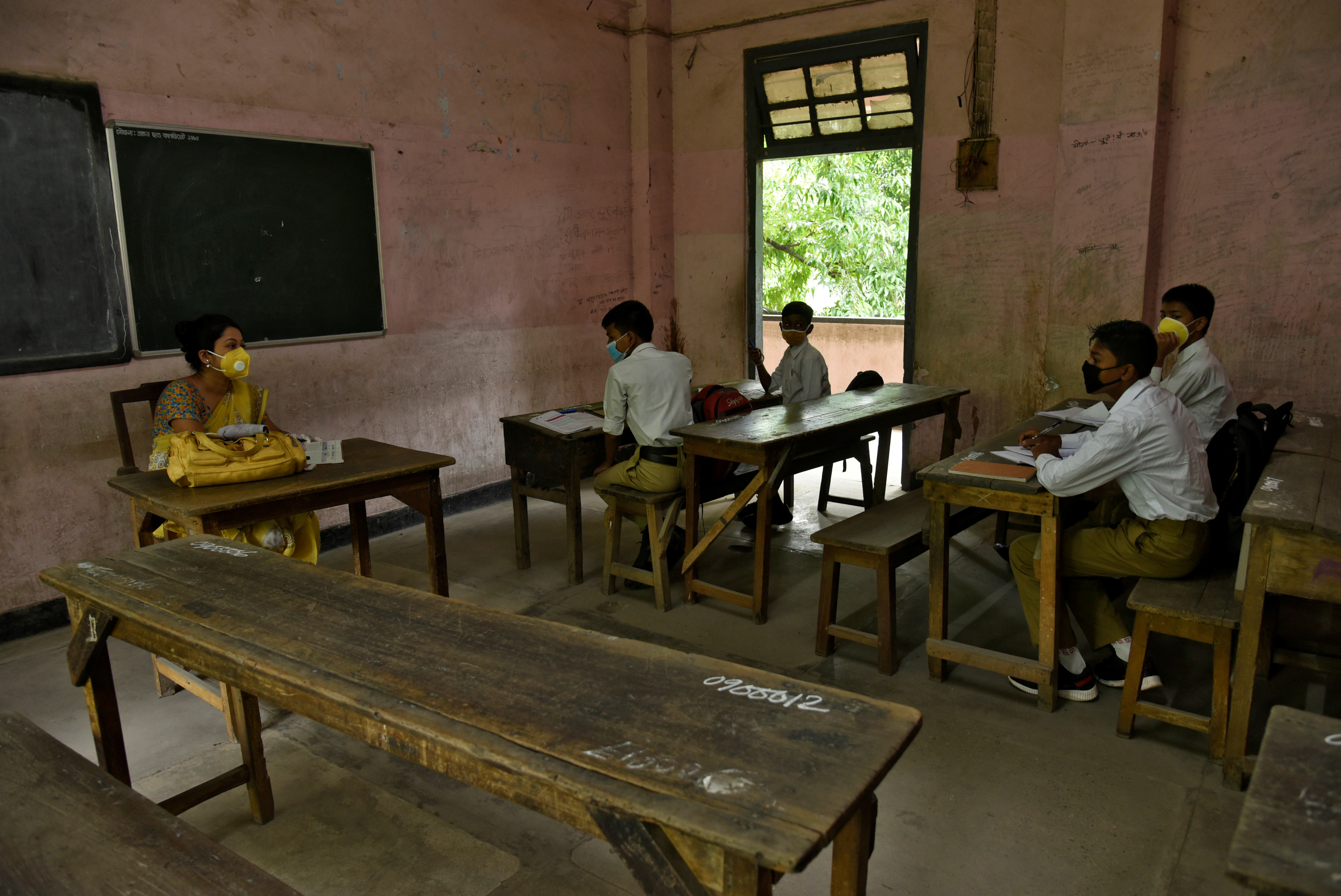 Students and their teacher wear protective face masks inside a classroom to stop the spread of covid-19