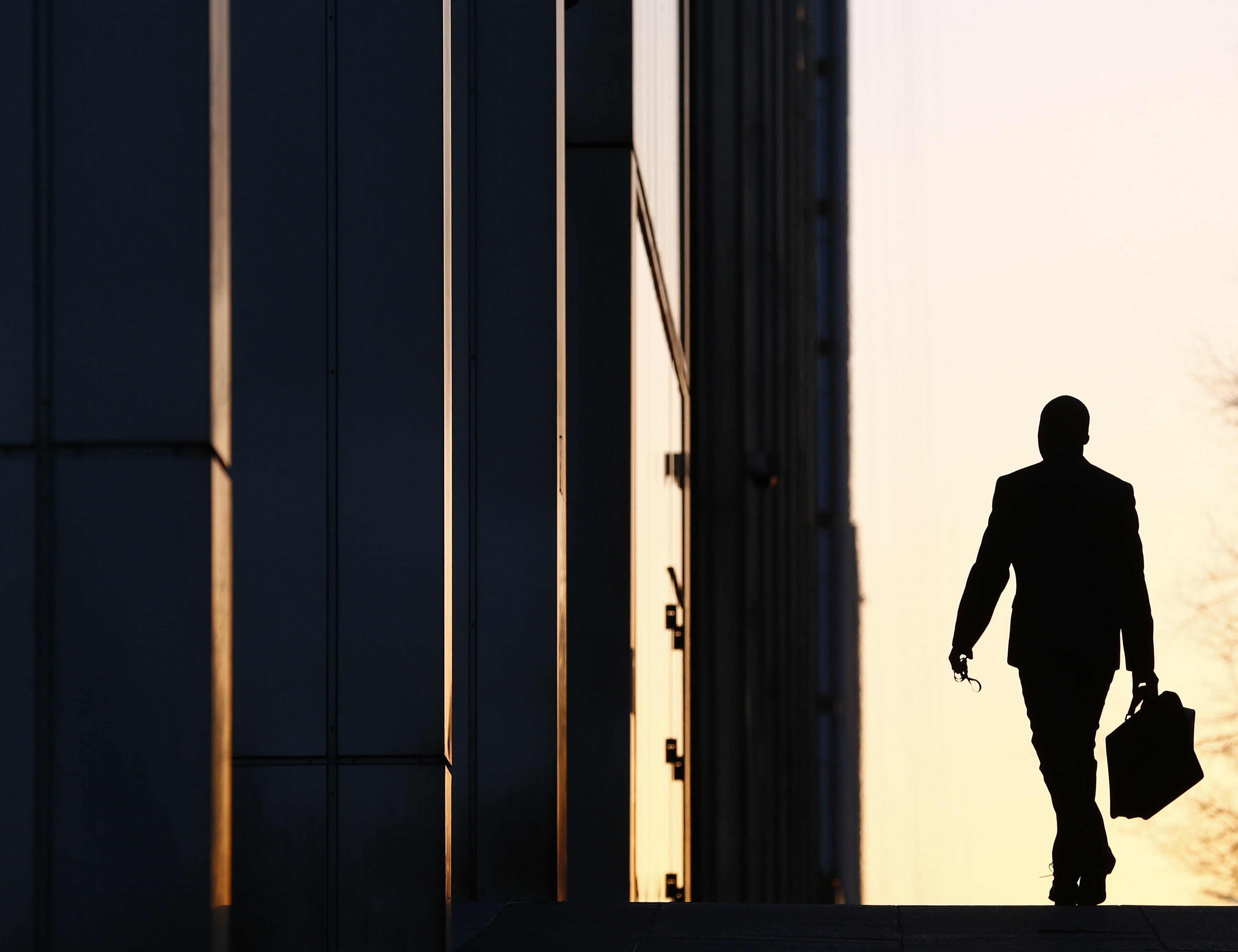 a person carrying a briefcase as they walk among office buildings
