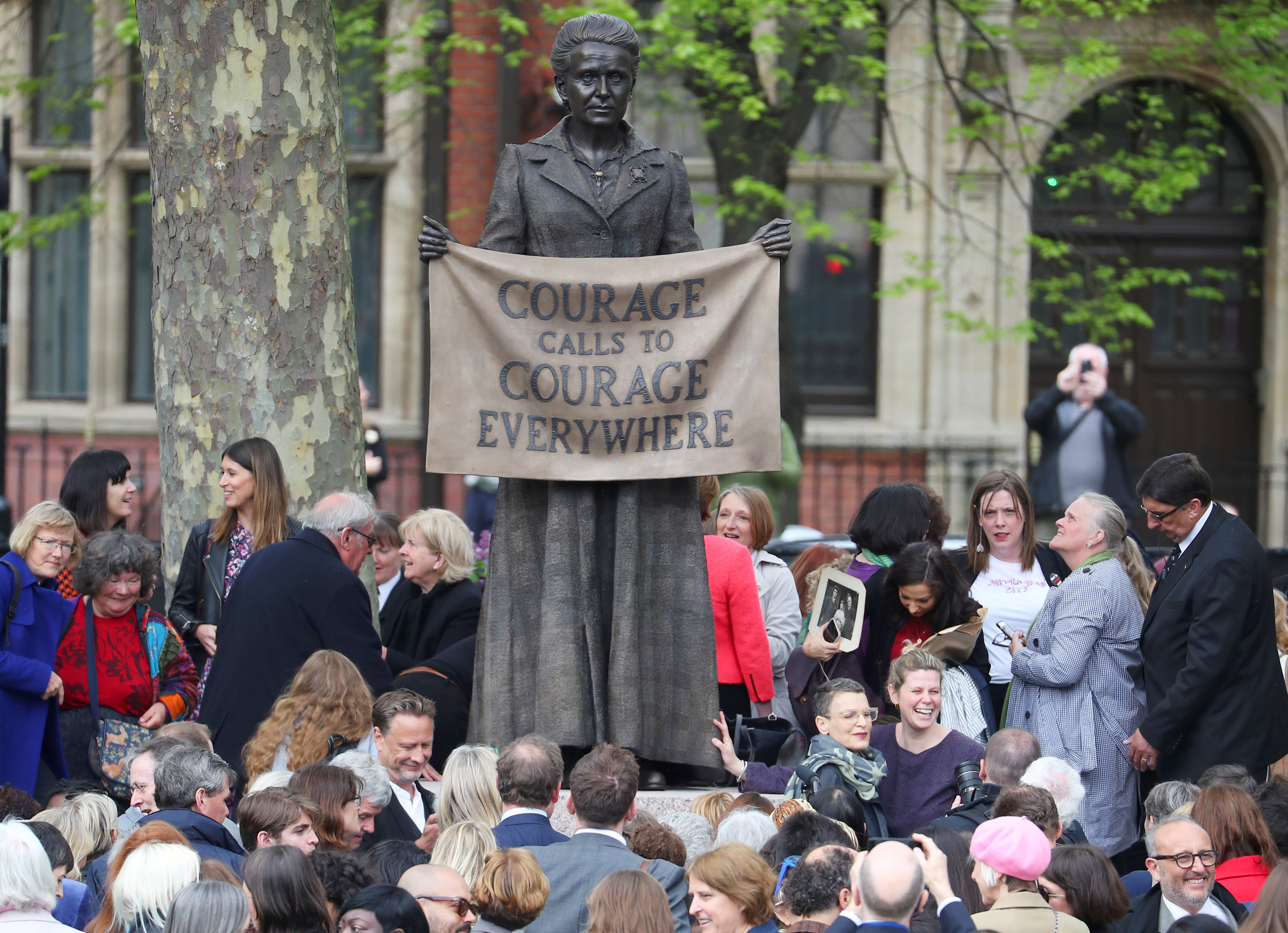 People attending the official unveiling gather around the statue of suffragist Millicent Fawcett on Parliament Square