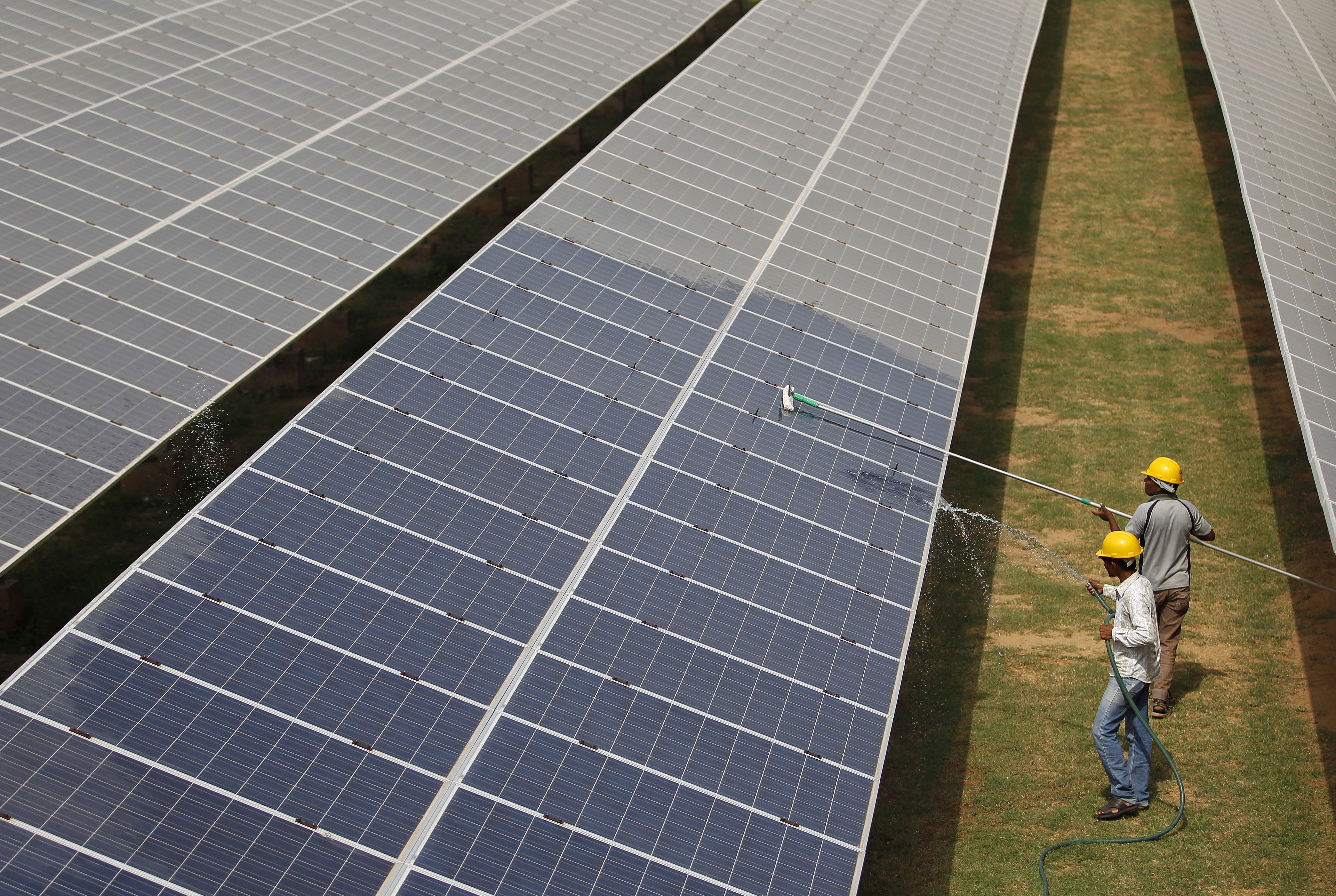 Workers clean photovoltaic panels inside a solar power plant in Gujarat, India,