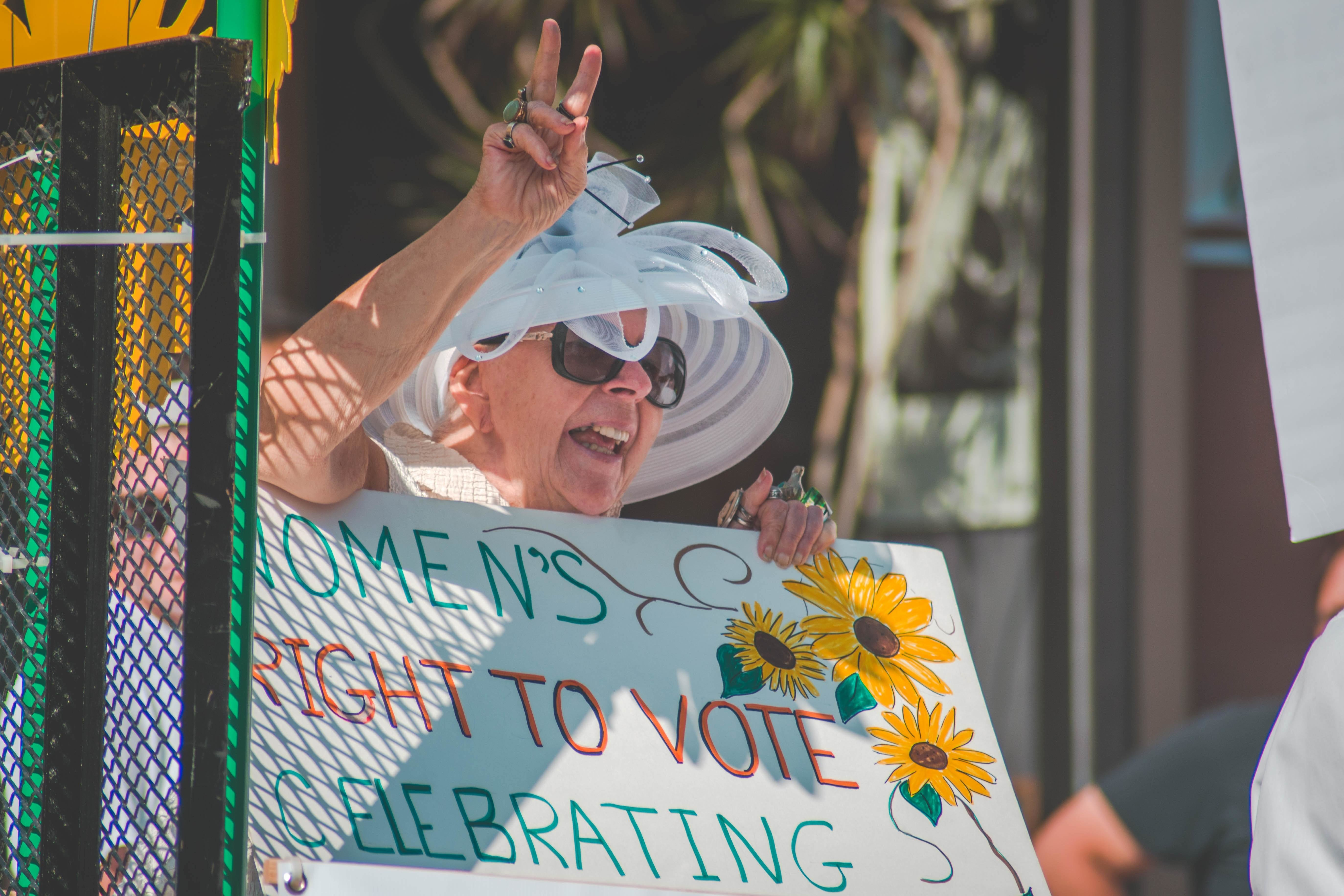 image of a woman holding up a sign celebrating women's right to vote