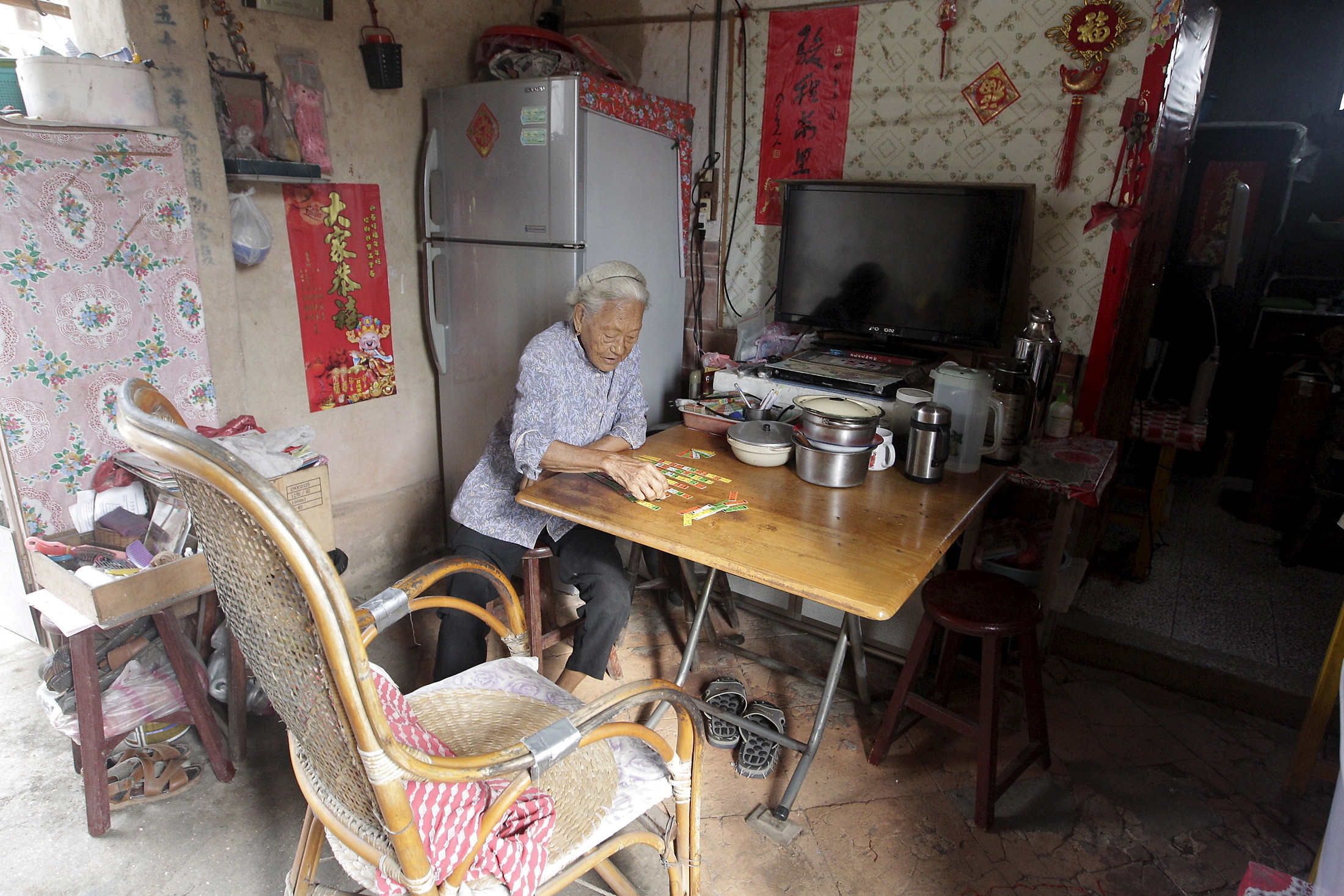 An elderly woman plays cards in a village in Taiwan.