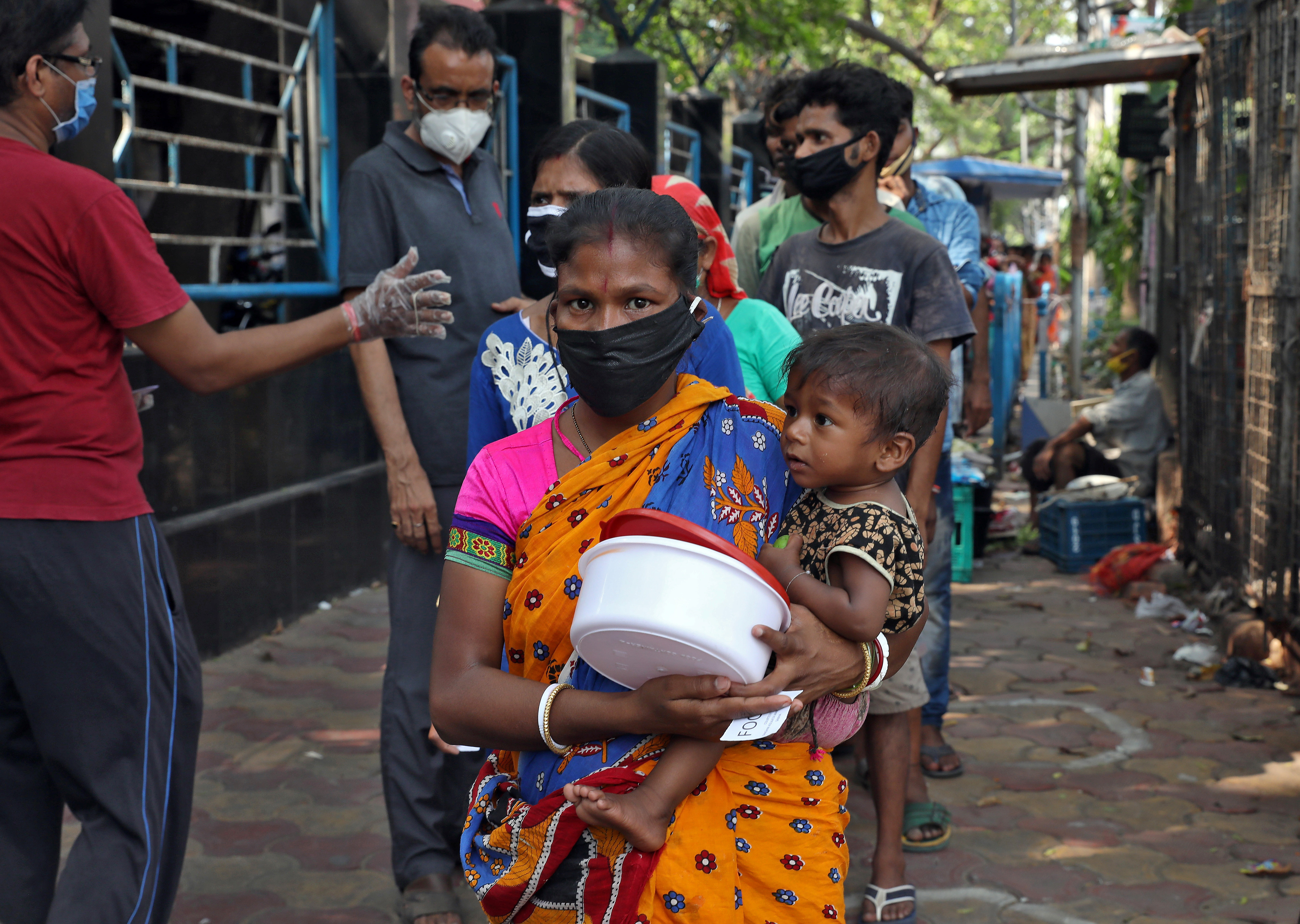 A homeless woman holding a child waits to receive food during a 21-day nationwide lockdown to slow the spreading of the coronavirus disease (COVID-19) in Kolkata, India, April 3, 2020. REUTERS/Rupak De Chowdhuri - RC2YWF9E1LI6