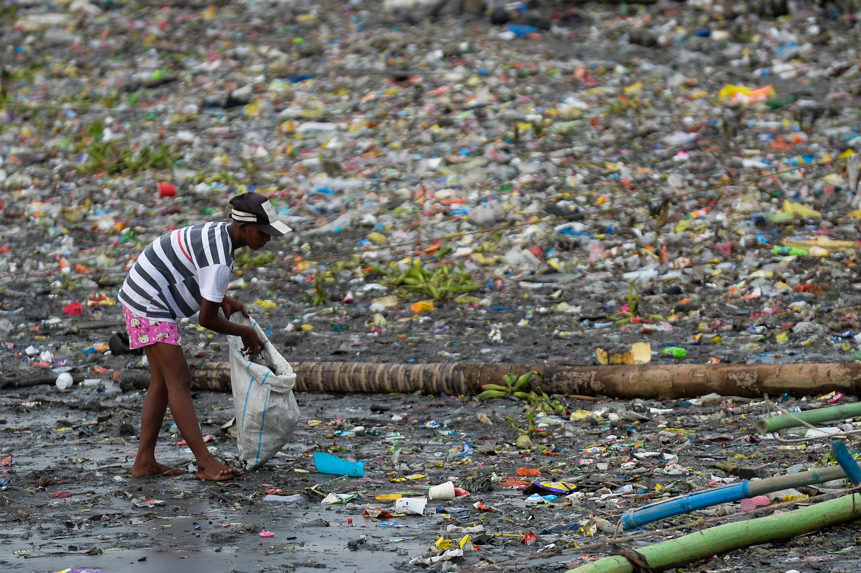 a woman picks up plastic in a heavily plastic polluted area hi-lighting the issue of plastic pollution worldwide