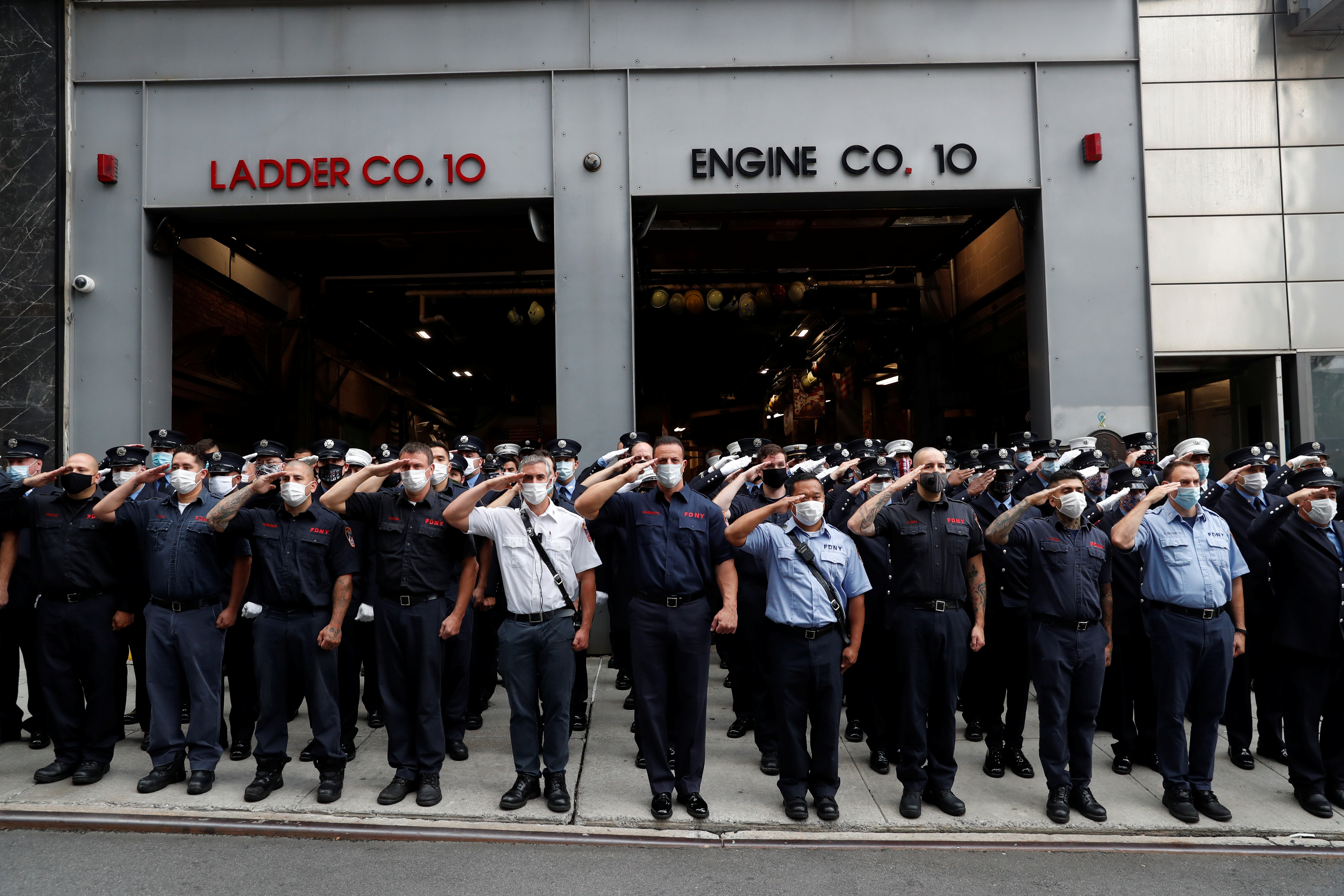 New York City Fire Department (FDNY) firefighters salute outside Ladder Co. 10, Engine Co. 10 on the 19th anniversary of the September 11, 2001 attacks on the World Trade Center in the Manhattan borough of New York City, New York, U.S., September 11, 2020. REUTERS/Shannon Stapleton - RC2CWI9L2HI7