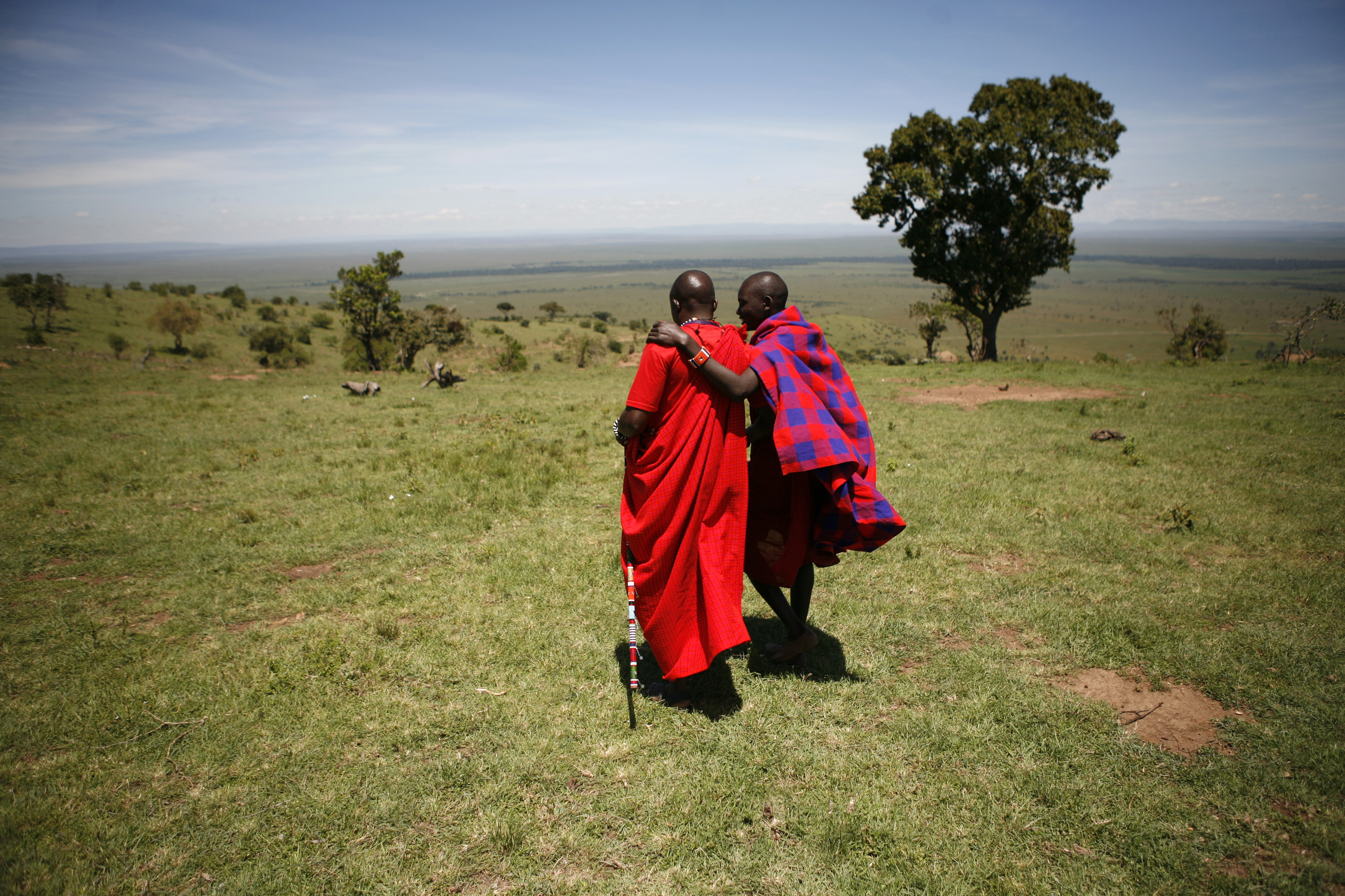 Two Maasai men walk outside Enkereri village near Masai Mara Game Reserve April 3, 2008.A rocky cliff overlooking the Reserve marks a new front line in a conflict between people and wildlife that threatens the revival of Kenya's $1 billion tourism industry. Riots and ethnic violence that exploded after a disputed December 27 vote scared away almost all the foreign holidaymakers. The disappearance of tourist dollars has disturbed the delicate balance between predators in the reserve and the Maasai tribesmen living next to it, by causing the breakdown of a compensation scheme meant to stop them hunting lions. Picture taken April 3, 2008. To match feature KENYA-WILDLIFE/ REUTERS/Radu Sigheti (KENYA ENVIRONMENT TRAVEL POLITICS)  BEST QUALITY AVAILABLE - GM1E57T1ECV01