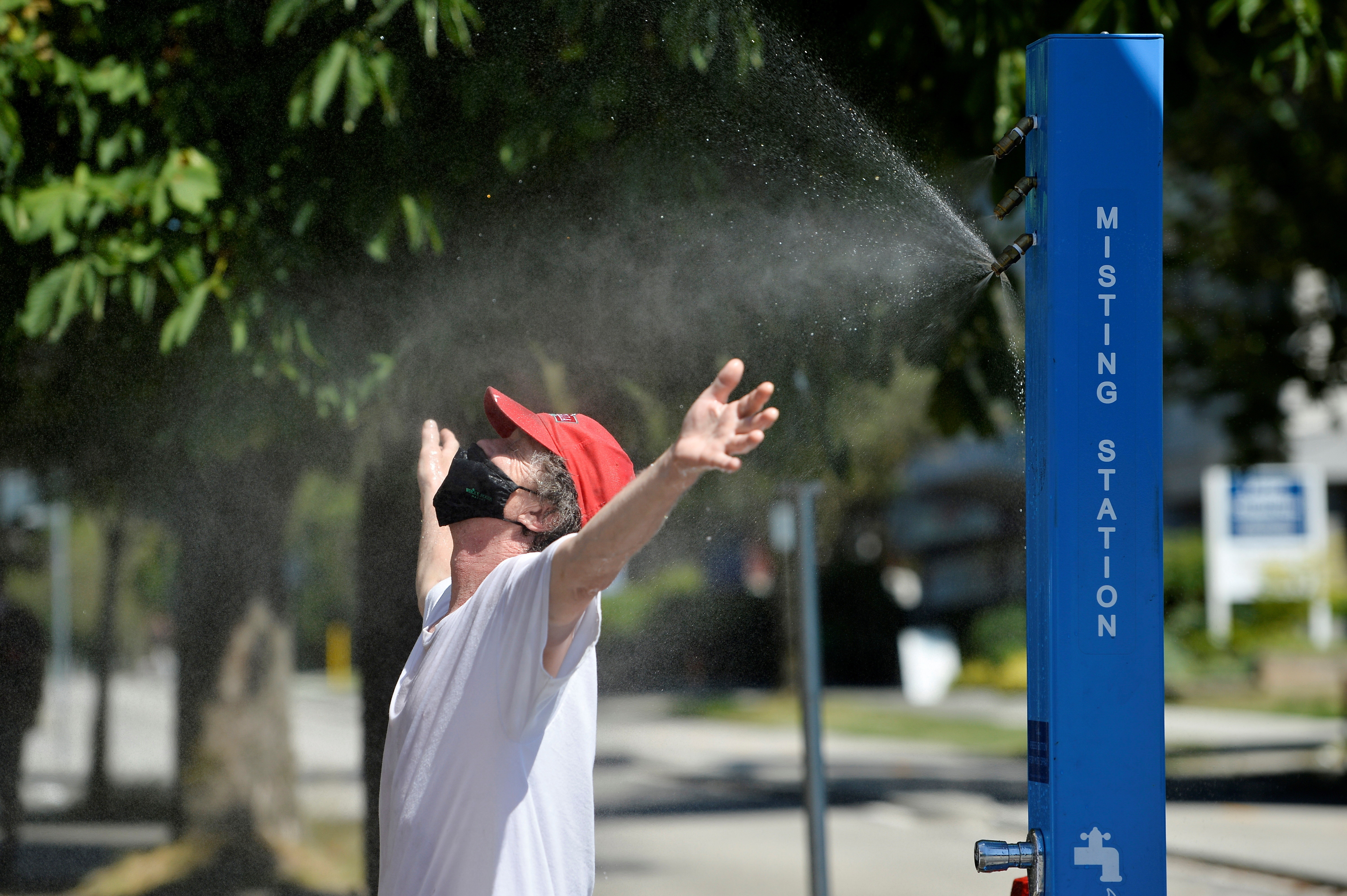 A man cools off at a misting station during the scorching weather of a heatwave in Vancouver, British Columbia, Canada