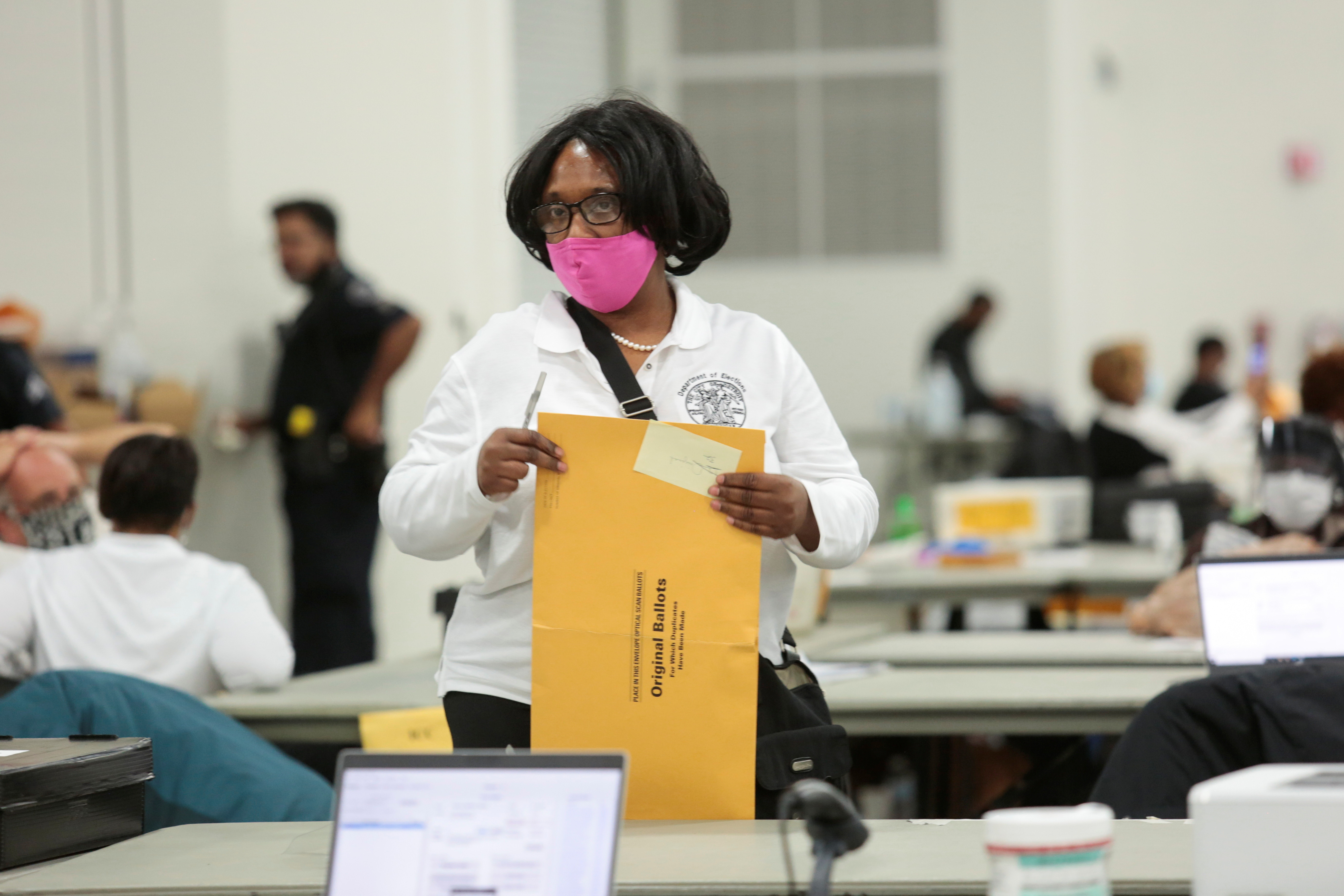 A poll worker supervisor looks on as she handles an envelope of original ballots at the TCF center after Election Day in Detroit, Michigan, U.S., November 4, 2020. REUTERS/Rebecca Cook - RC2OWJ9516M2