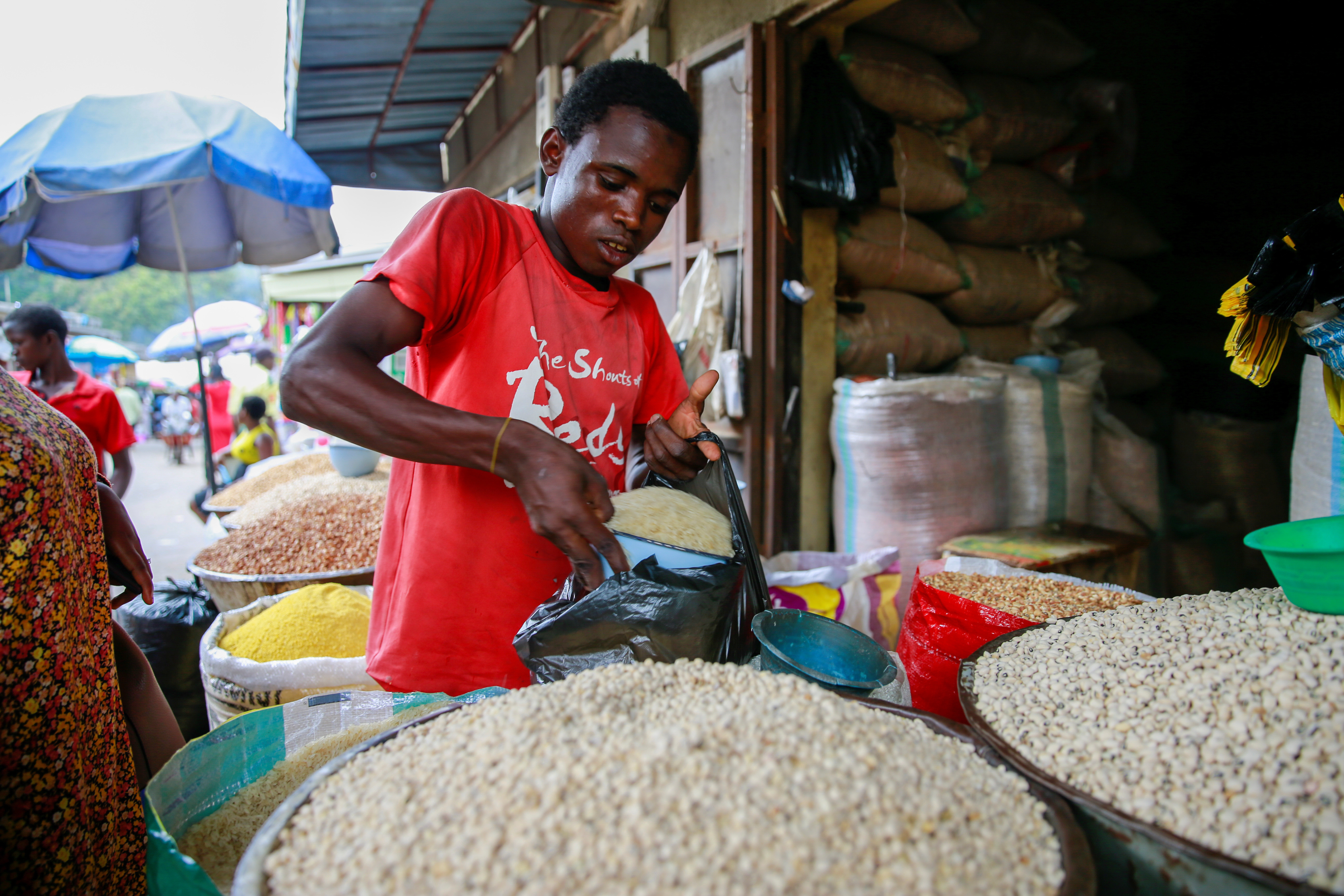 A man measures out a bowl of rice grains into a bag at a grains shop in Garki market Abuja, Nigeria November 13, 2019. Picture taken November 13, 2019.