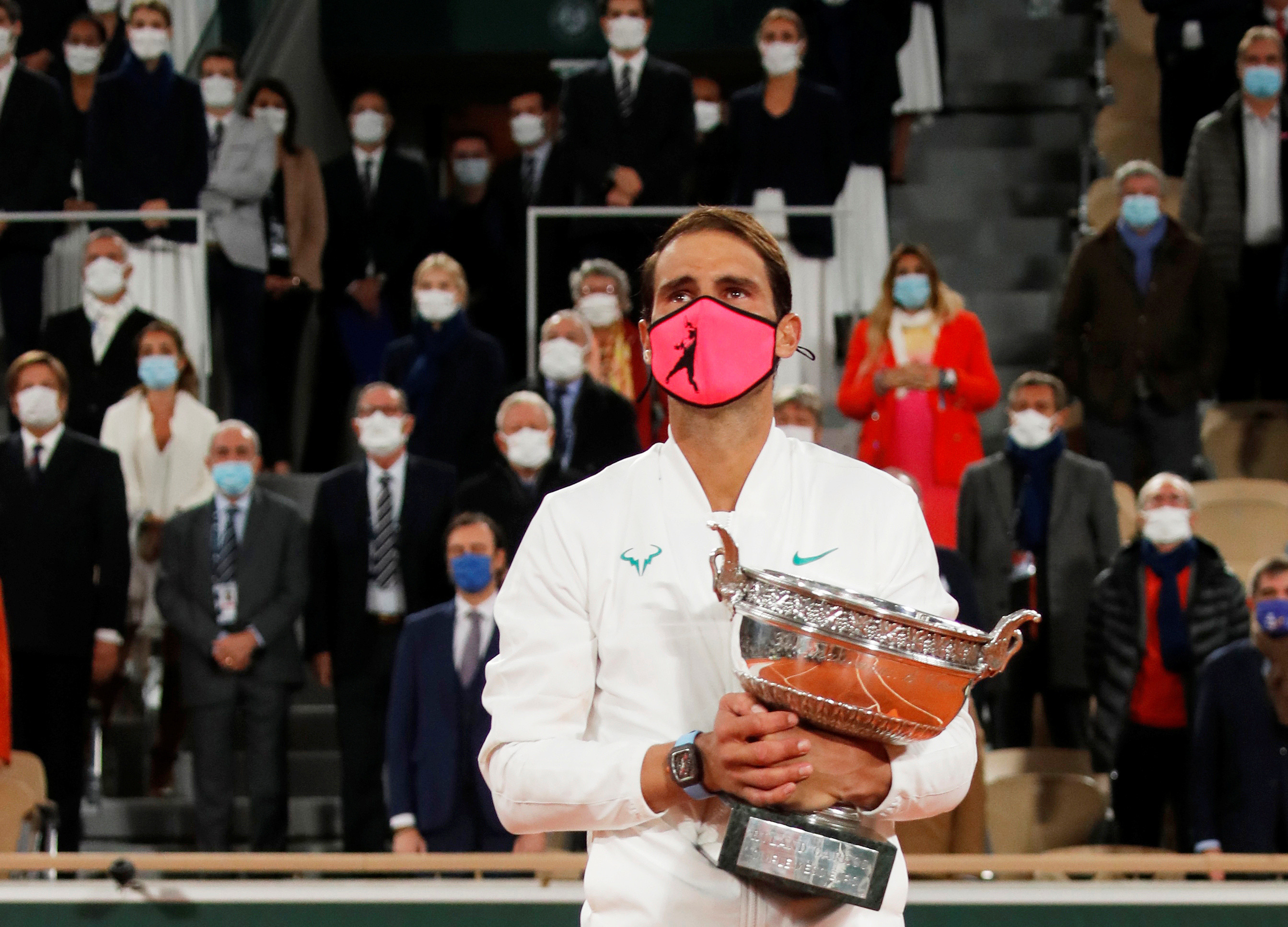 Spanish tennis player Rafael Nadal holds the trophy, while wearing a mask, after winning the French Open against Serbia's Novak Djokovic.
