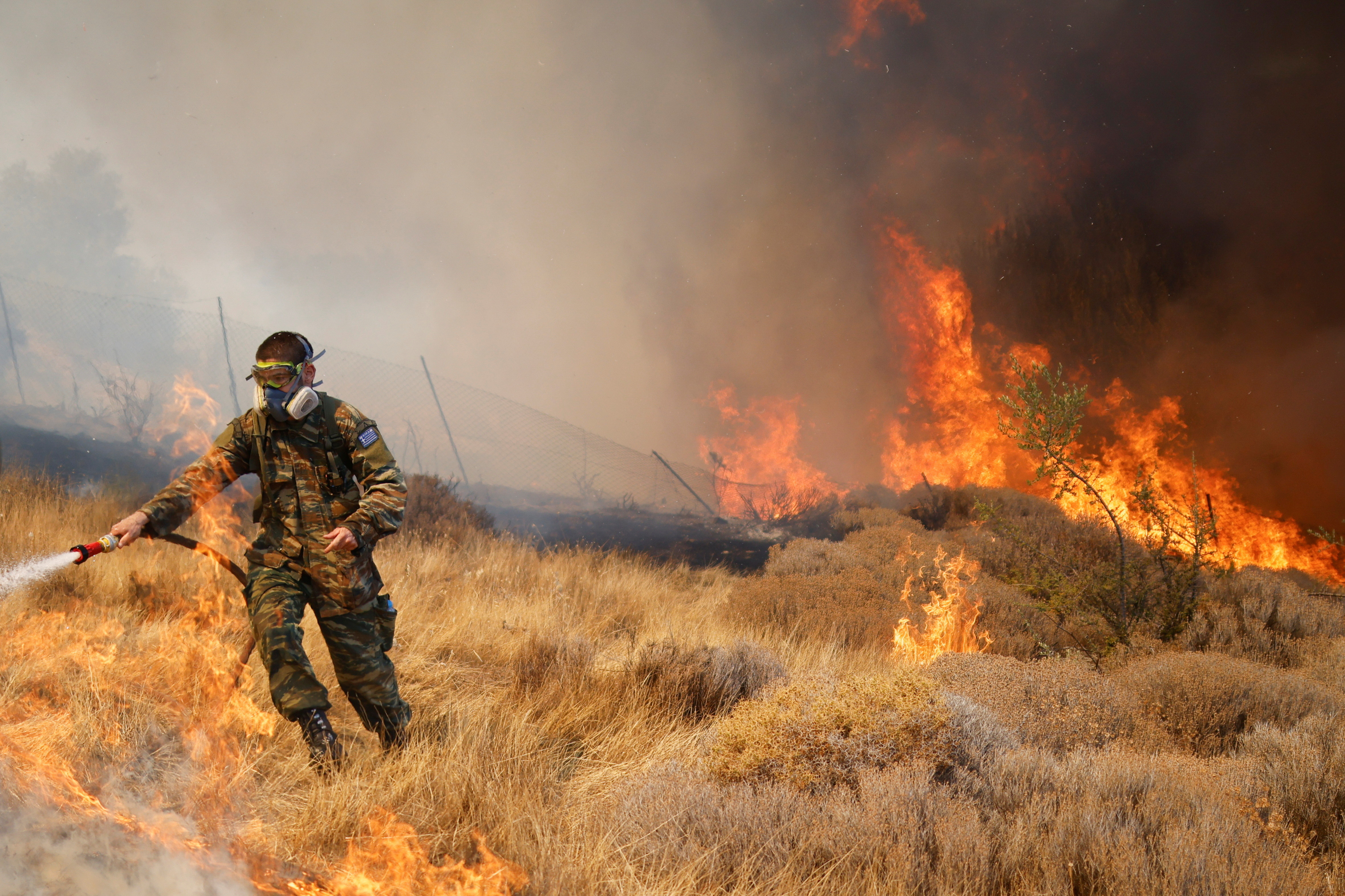 A volunteer tries to extinguish a wildfire burning in the village of Markati, near Athens, Greece, August 16, 2021.