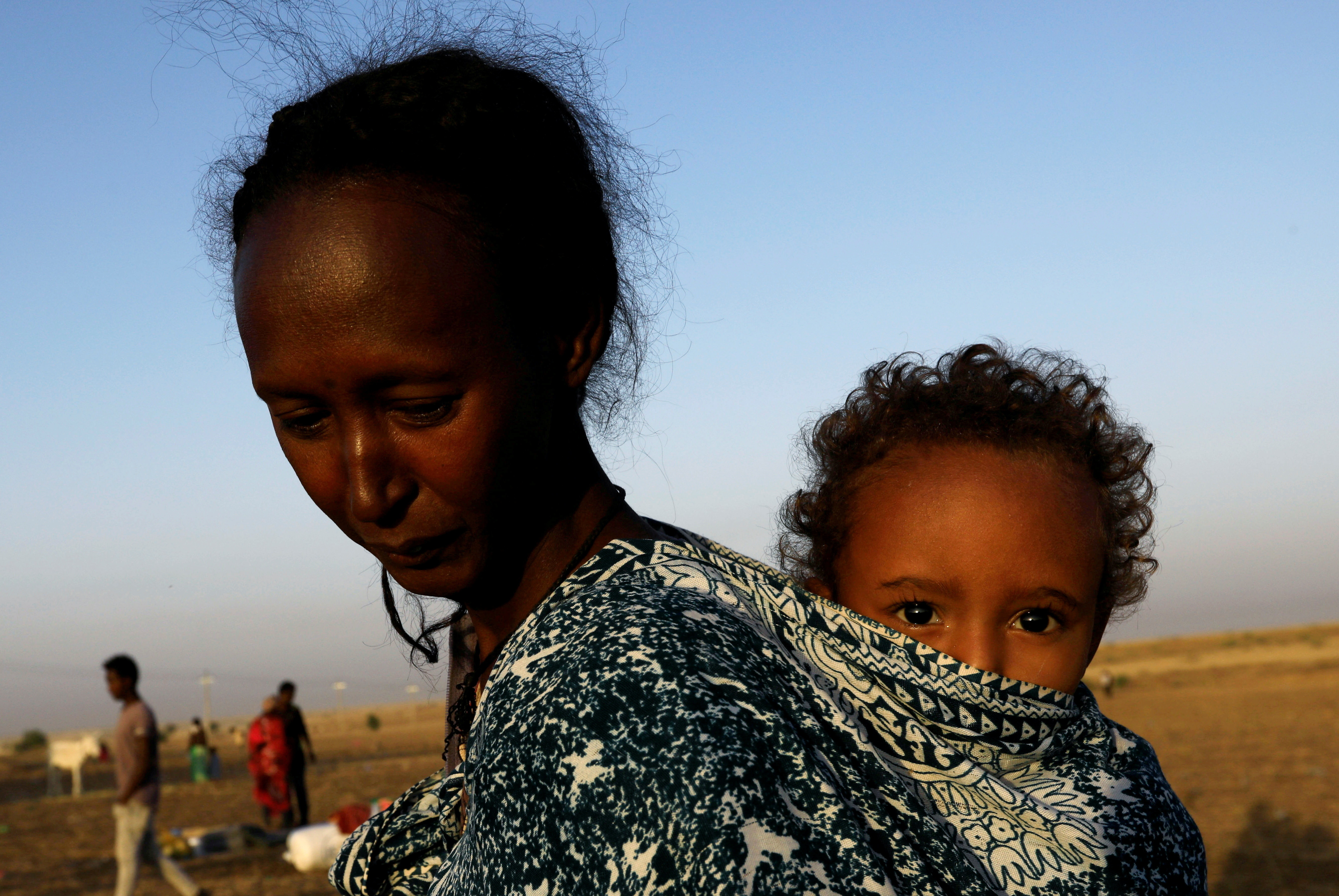 a woman carries a child on her back