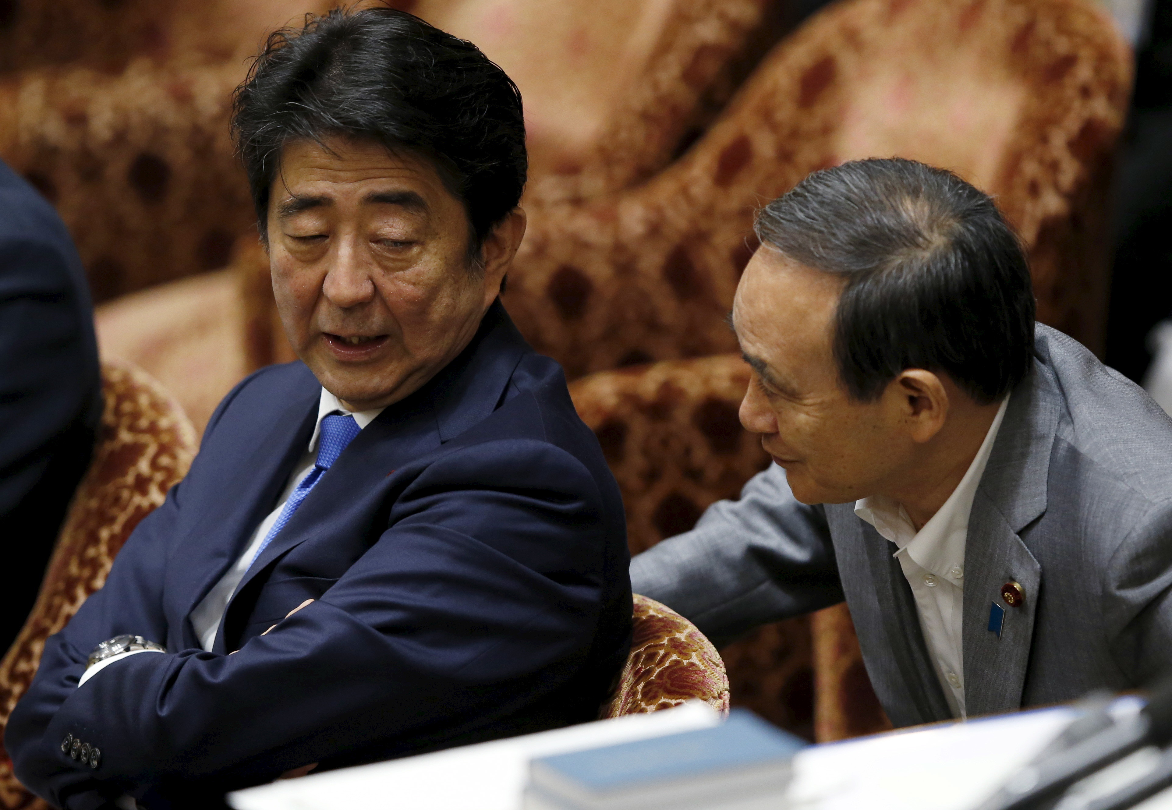 Japan's Prime Minister Shinzo Abe (L) talks with Chief Cabinet Secretary Yoshihide Suga at a lower house special committee session on security-related legislation at the parliament in Tokyo July 15, 2015. Abe faces his toughest challenge since taking office in 2012 as his ruling bloc prepares to force unpopular security bills through the lower house despite voter doubts about the legislation and a slew of other policies. REUTERS/Toru Hanai - GF10000159484