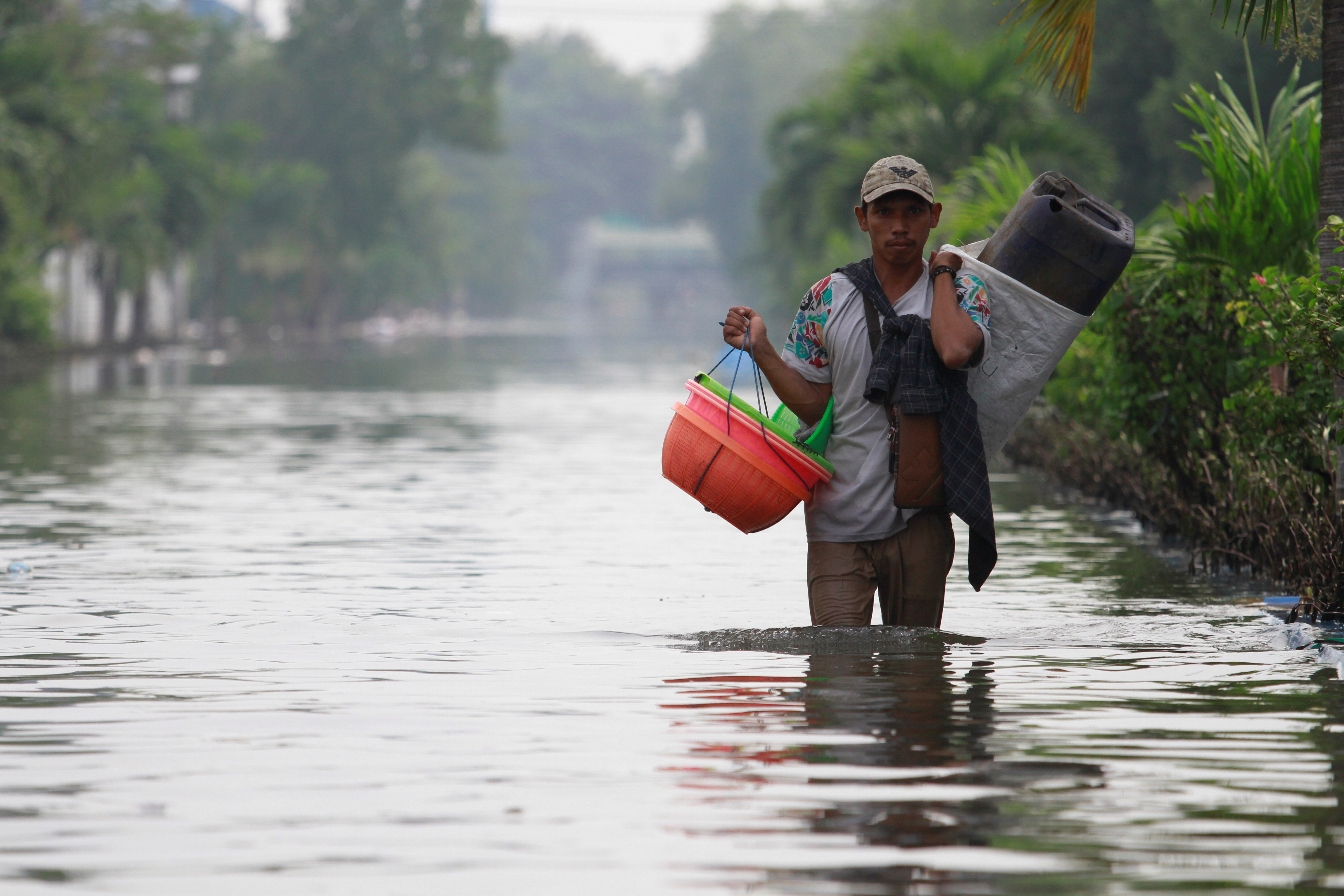 A man carries baskets through a flooded road, at an area affected by land subsidence and rising sea level in North Jakarta, Indonesia, June 5, 2020. REUTERS/Ajeng Dinar Ulfiana - RC2Y2H9Z3F92