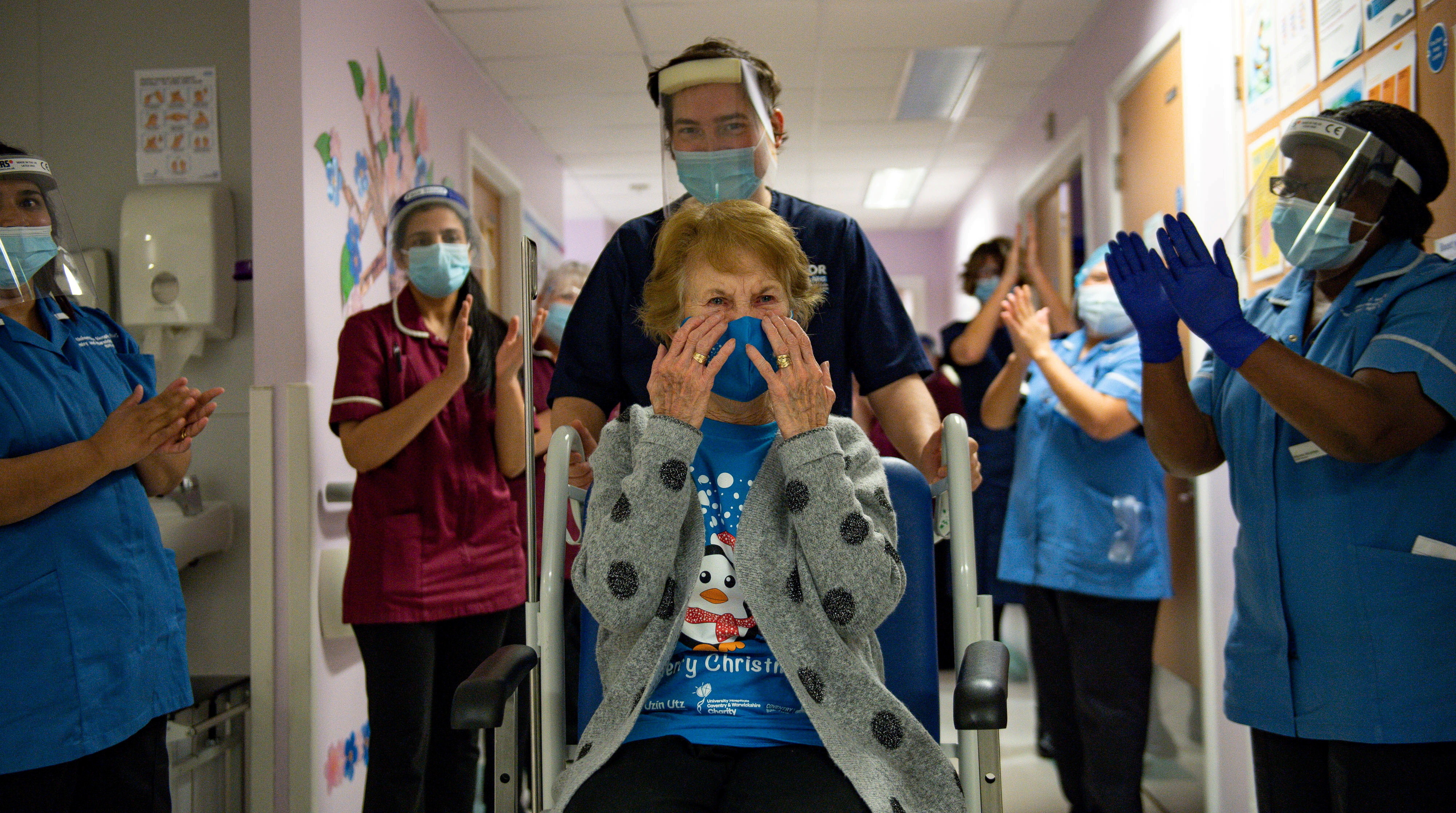 Margaret Keenan, 90, is applauded by staff as she returns to her ward after becoming the first person in Britain to receive the Pfizer/BioNTech  COVID-19 vaccine at University Hospital, at the start of the largest ever immunisation programme in the British history, in Coventry, Britain December 8, 2020. Britain is the first country in the world to start vaccinating people with the Pfizer/BioNTech jab. Jacob King/Pool via REUTERS     TPX IMAGES OF THE DAY - RC2XIK99JVEQ