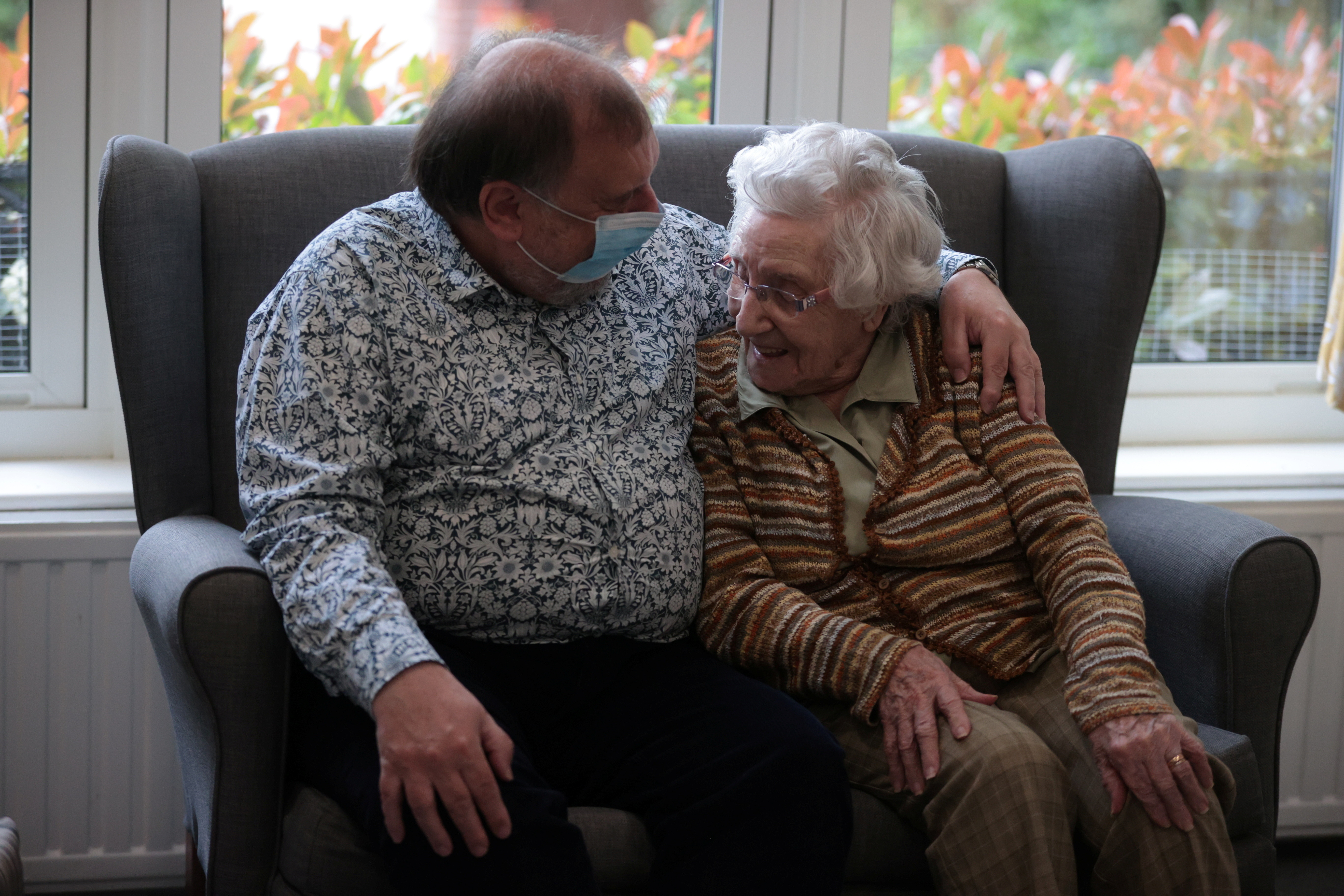 a man embraces his elderly mother at a care home
