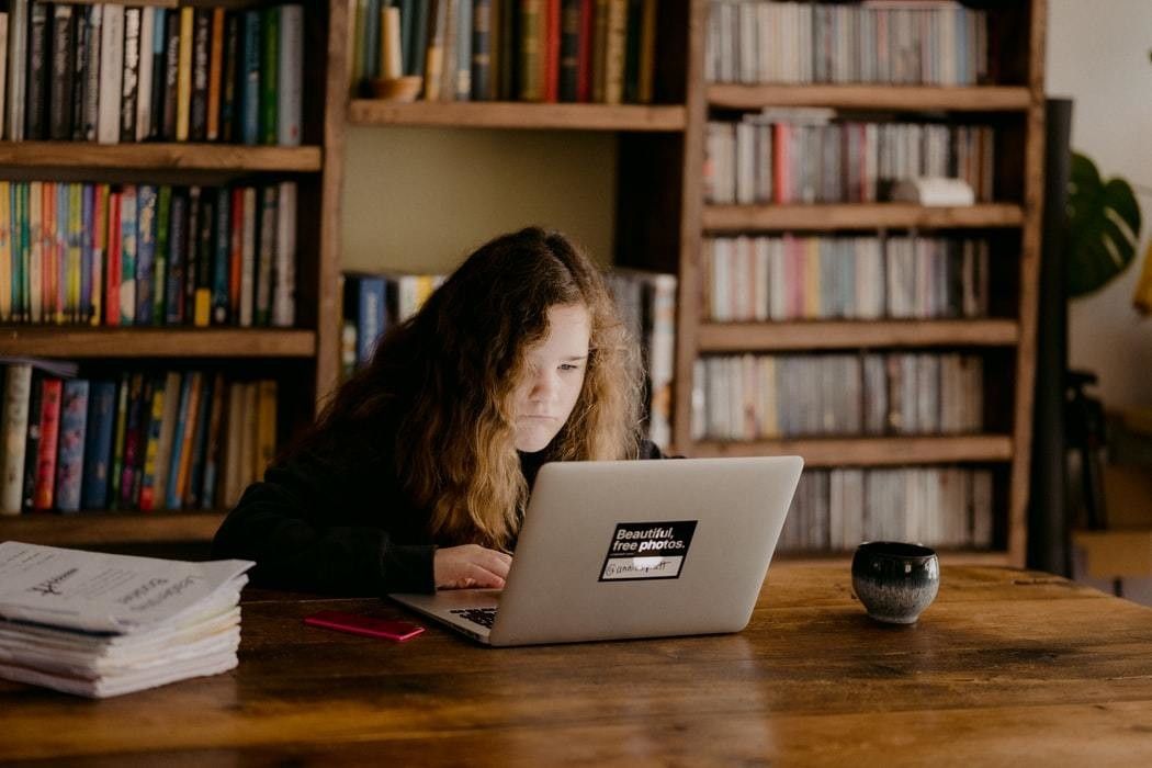 Young teen doing schoolwork at home after UK schools close due to the Coronavirus..