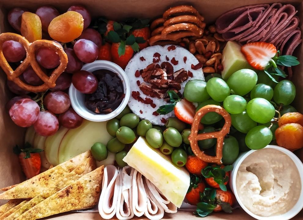 A variety of food including cheese, ham, grapes, olives, bread.